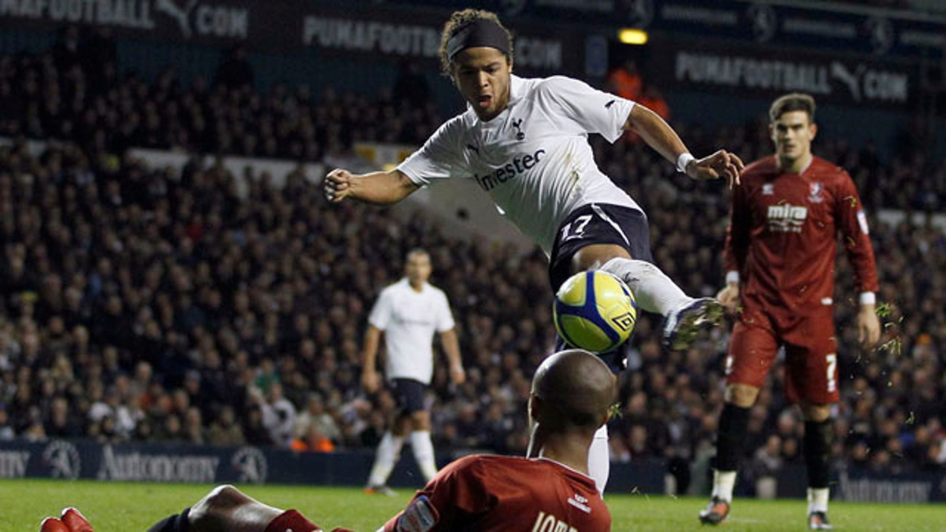 Tottenham Hotspur's Giovani Dos Santos, top, vies for the ball with Cheltenham Town's Sido Jombati during the English FA Cup third round soccer match at White Hart Lane Stadium in London, Saturday Jan. 7, 2012. (AP Photo/Kirsty Wigglesworth)