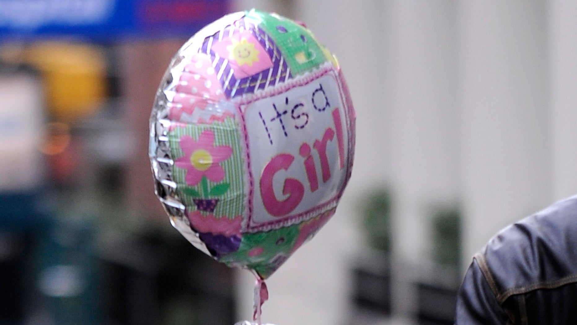 """08 January 2012 - New York - A man with """"It's a girl"""" baloons walked out of Lenox Hill Hospital entrance on 77th Street between Lexington Avenue and Park Avenue where singer Beyonce gave birth to daughter Blue Ivy Carter on January 7, 2012,  New York, NY. Photo Credit: Anthony Behar/Sipa Press"""