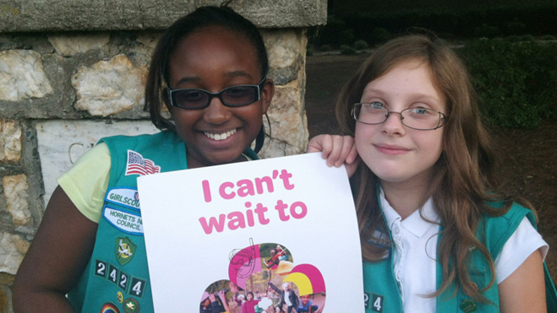 Sept. 27, 2013: In this photo provided by the Girl Scouts, Natalie Harrison, left, and Jasmine Barnett of Troop 2424 hold a promotional poster for their organization outside of Matthews Elementary School in Charlotte, N.C. The fifth graders were volunteering at a Girl Scout Informational night at the school to share their stories about their experiences in the group. Instead of placing ads on TV, in newspapers and on billboards, a decentralized campaign aimed at reversing a long-running decline in participation in the Girl Scouts will unfold in neighborhood initiatives and on social media as local councils directly target elementary school girls - even kindergartners - with promises of adventuresome fun.