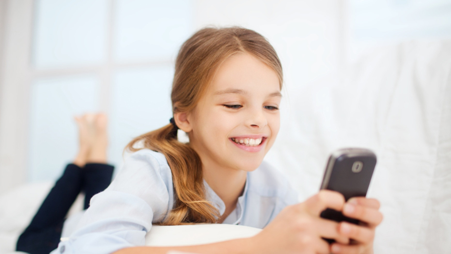 education, school, technology and internet concept - little student girl with smartphone at home