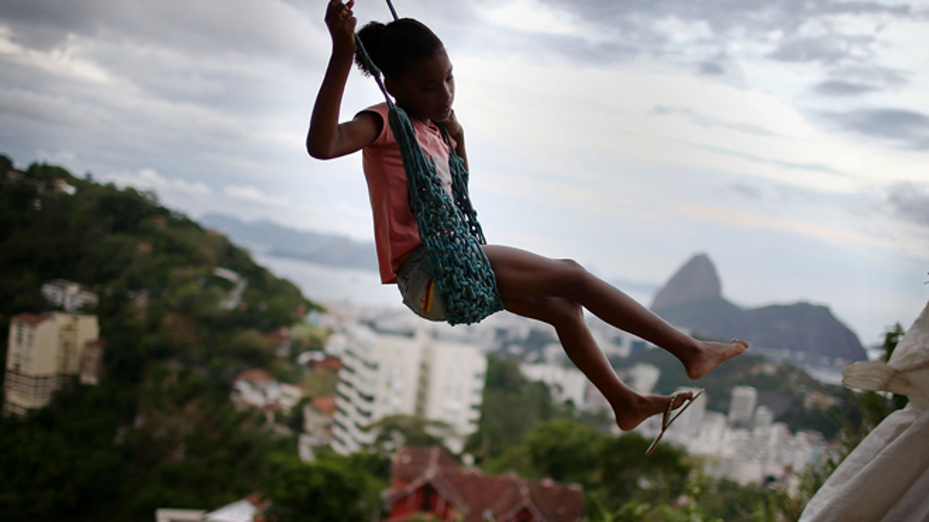 RIO DE JANEIRO, BRAZIL - MARCH 22:  A child swings on a swing in the Prazeres pacified 'favela' community on March 22, 2014 in Rio de Janeiro, Brazil. The 'favela' was previously controlled by drug traffickers and is now occupied by the city's Police Pacification Unit (UPP). A number of UPP's were attacked by drug gang members on March 20 and some pacified favelas will soon receive federal forces as reinforcements. The UPP are patrolling some of Rio's favelas amid the city's efforts to improve security ahead of the 2014 FIFA World Cup and 2016 Olympic Games.  (Photo by Mario Tama/Getty Images)