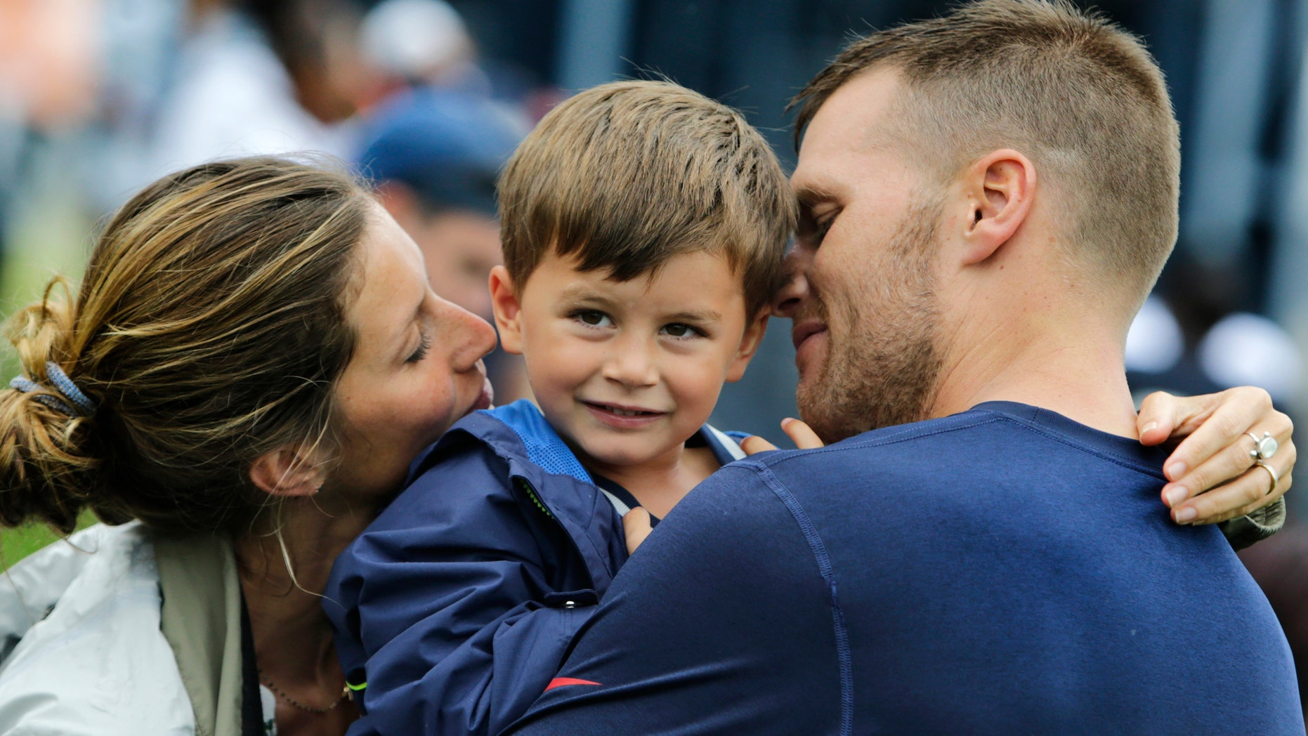 New England Patriots quarterback Tom Brady and his wife Gisele Bundchen embrace their son Benjamin Brady after a joint workout with the Tampa Bay Buccaneers at NFL football training camp, in Foxborough, Mass., Tuesday, Aug. 13, 2013. (AP Photo/Charles Krupa)