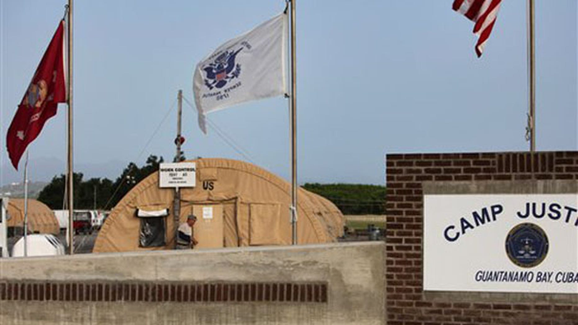FILE: U.S. flags hang above the sign marking the Camp Justice compound at Guantanamo Bay Naval Base in Cuba. (AP Photo)