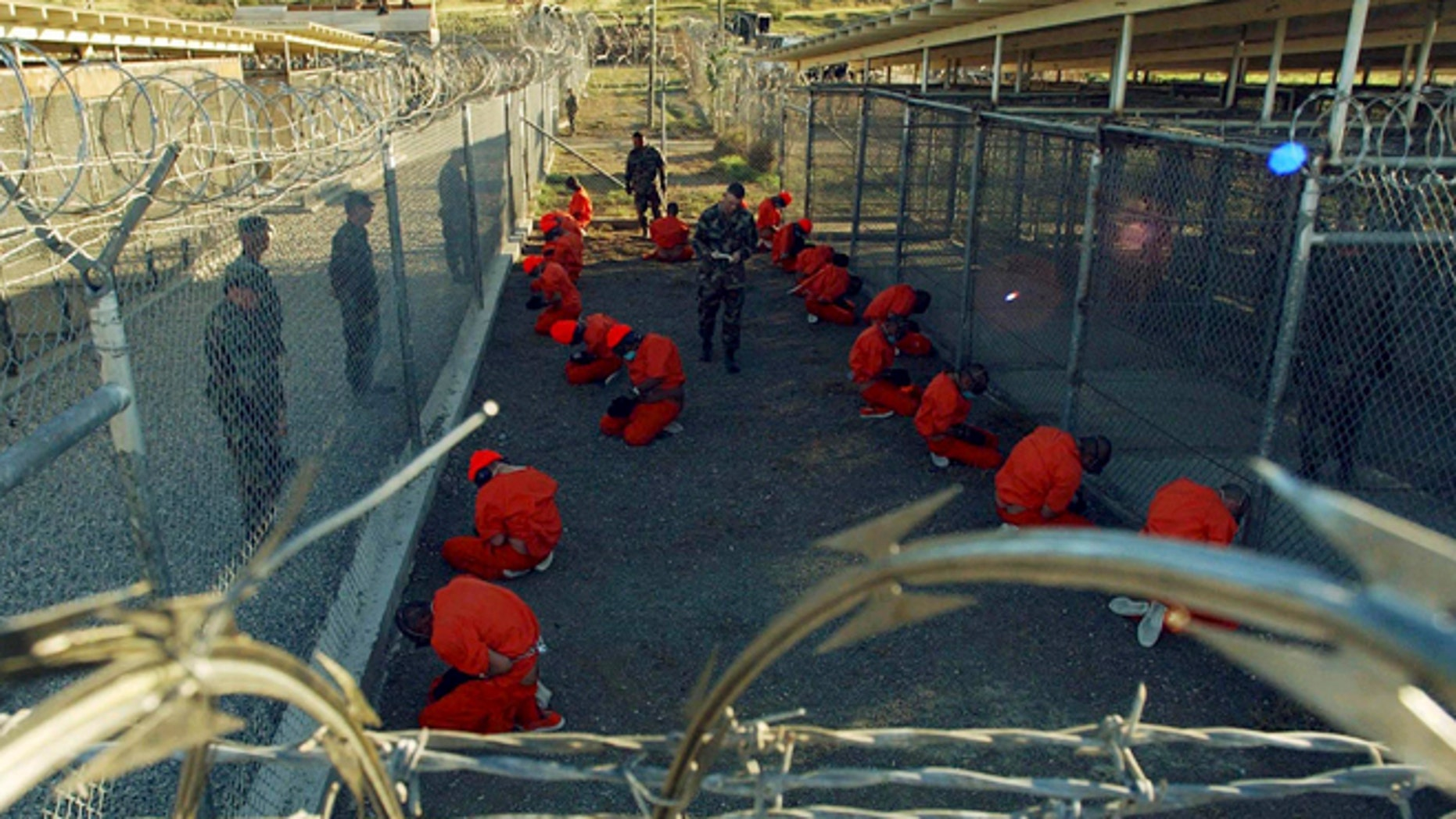 Jan 11, 2002: Detainees in orange jumpsuits sit in a holding area under the watchful eyes of military police during in-processing to the temporary detention facility at Camp X-Ray of Naval Base Guantanamo Bay. (Reuters)