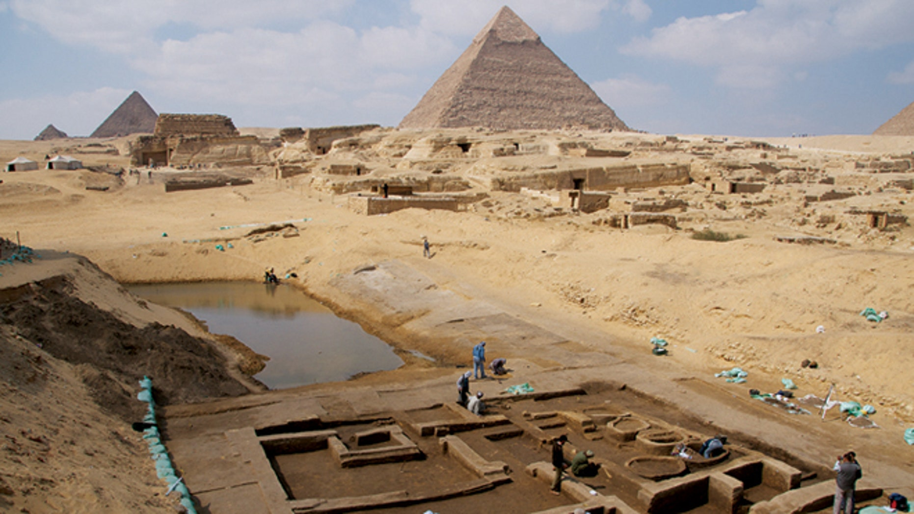 """Archaeologists working at the Giza Pyramids have made several new discoveries that shed light on life at the time the pyramids were built. Among the discoveries is a basin that may have been part of a thriving harbor and a """"silo building complex,"""" where researchers have found numerous bones from the forelimbs of cattle, offerings in ancient Egypt, suggesting royal cult priests perhaps venerating the pharaoh Khafre occupied the complex."""