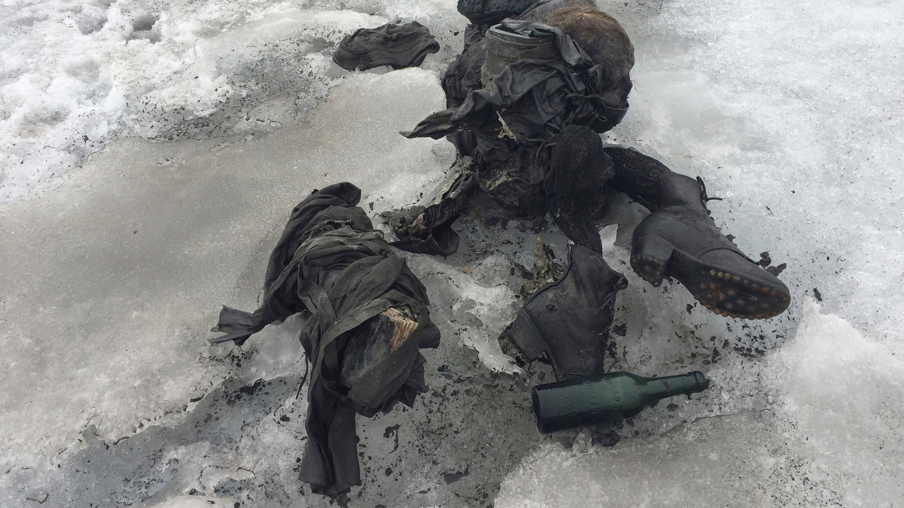 In this photo released by the Swiss train company ' Glacier 3000' shoes and clothing are visible at a Swiss glacier where two bodies were found. Police say the bodies of what appear to be two people killed in an accident decades ago have been recovered from a glacier in southwestern Switzerland. Valais canton police say the bodies were found on the Tsanfleuron glacier Friday July 14, 2017 at an altitude of 8,580 feet. They say the equipment found suggests that they died decades ago, and that formal identification with the help of DNA will take several days. (GLACIER 3000/Keystone via AP)