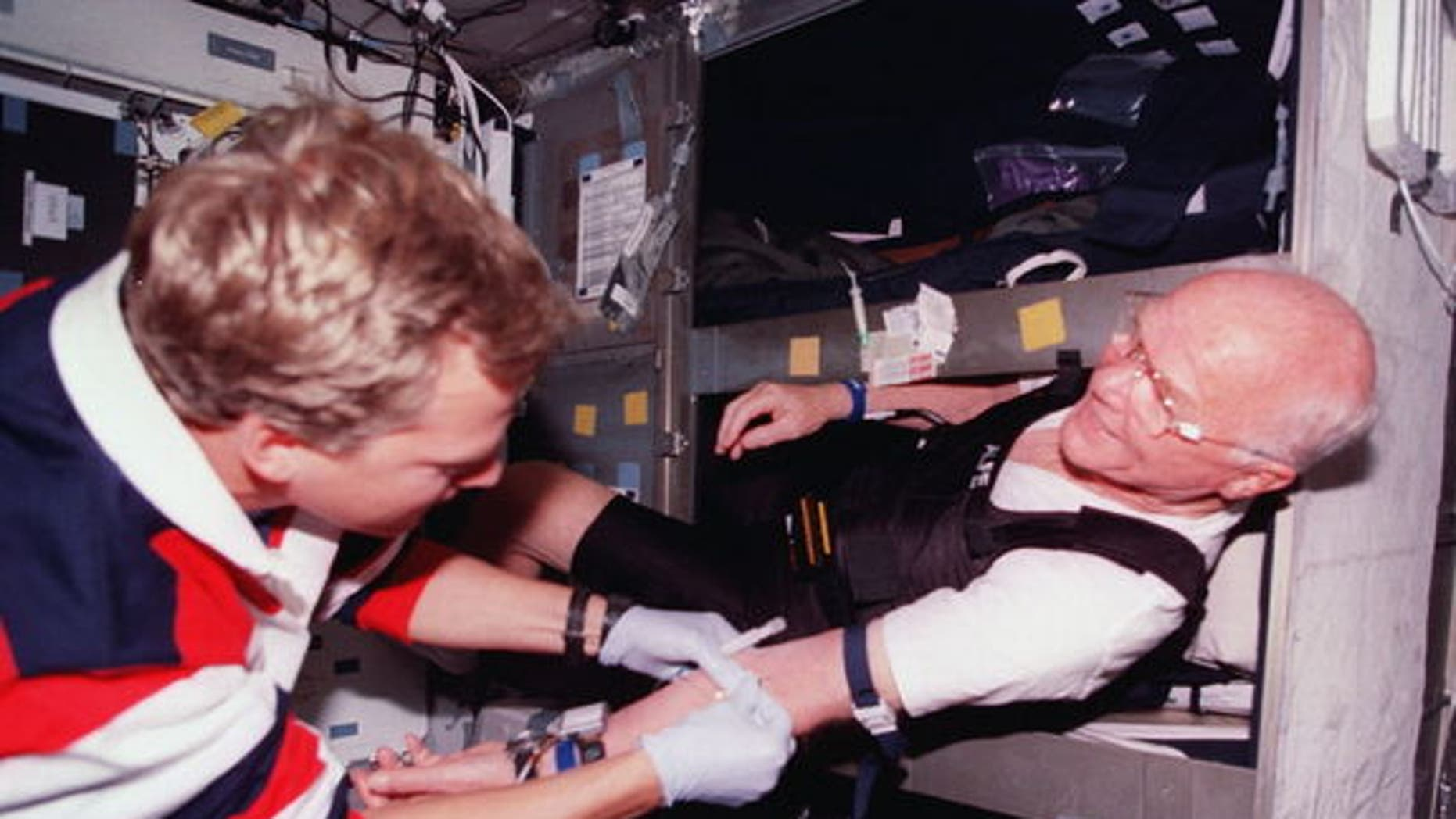 Astronaut John Glenn (right) gets bloodwork done in his bunk aboard space shuttle Discovery in 1998. About half of astronauts require sleep medication at some point during their flights, NASA said.