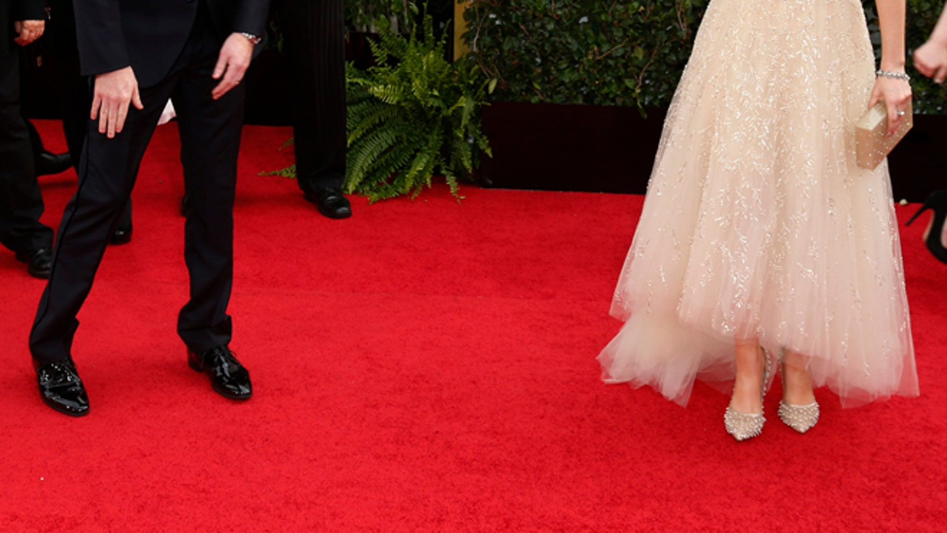 Actress Zooey Deschanel and actor Jesse Tyler Ferguson talk on the red carpet at the 71st annual Golden Globe Awards in Beverly Hills, California January 12, 2014.  REUTERS/Danny Moloshok  (UNITED STATES - Tags: Entertainment)(GOLDENGLOBES-ARRIVALS) - RTX17B5Z
