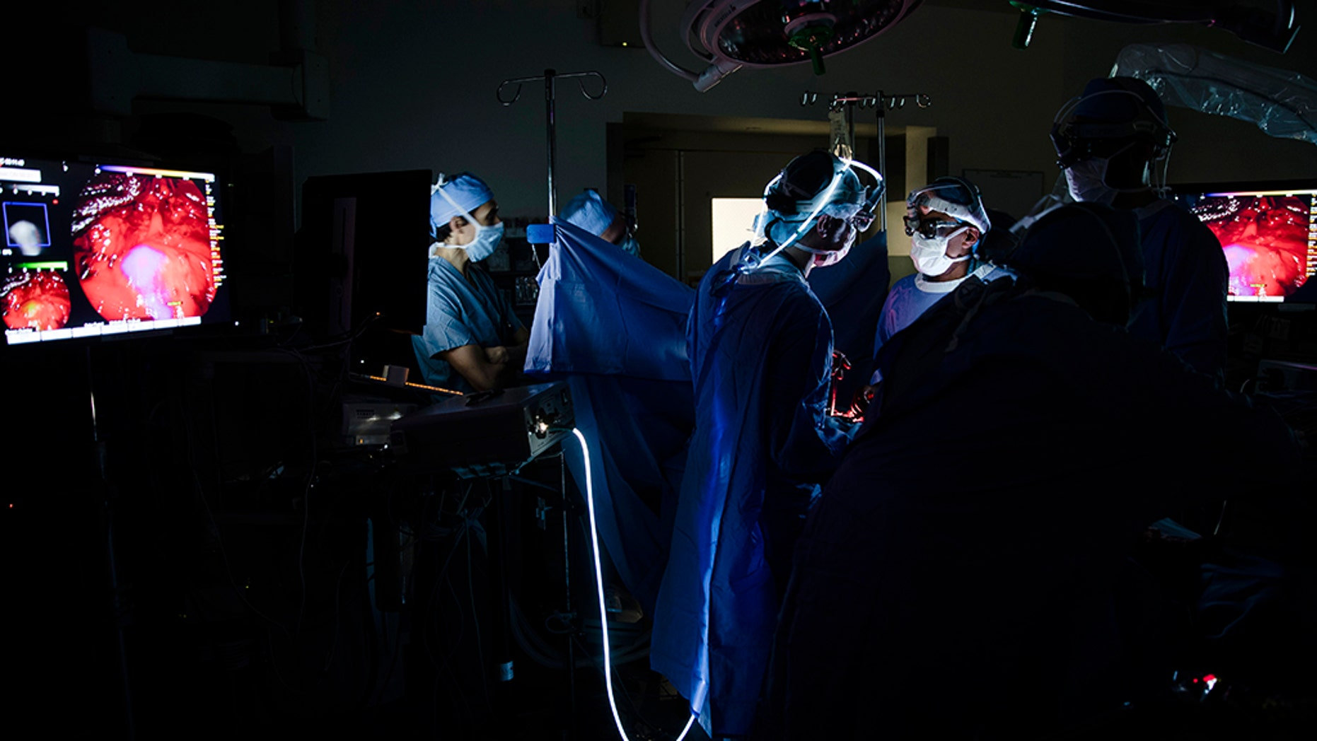 Dr. Sunil Singhal, second from right, directs a special camera to view a tumor in his patient made visible with a fluorescent dye, seen at monitor on right, at the Hospital of the University of Pennsylvania.