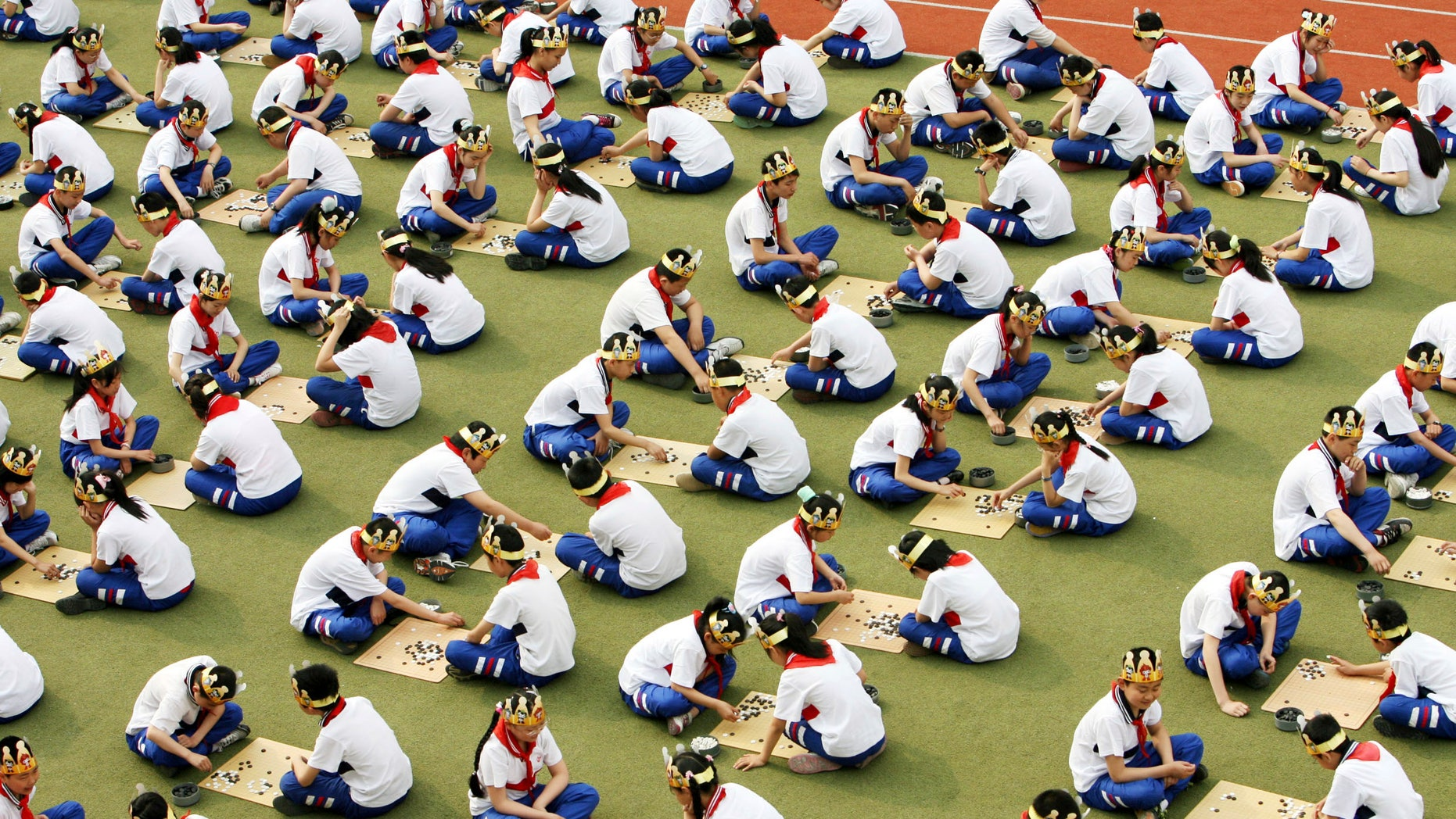 """Students play the board game """"Go"""", known as """"Weiqi"""" in Chinese, during a competition to mark the 100-day countdown to the opening of Beijing Olympics at a primary school in Suzhou, Jiangsu province. (REUTERS/China Daily)"""