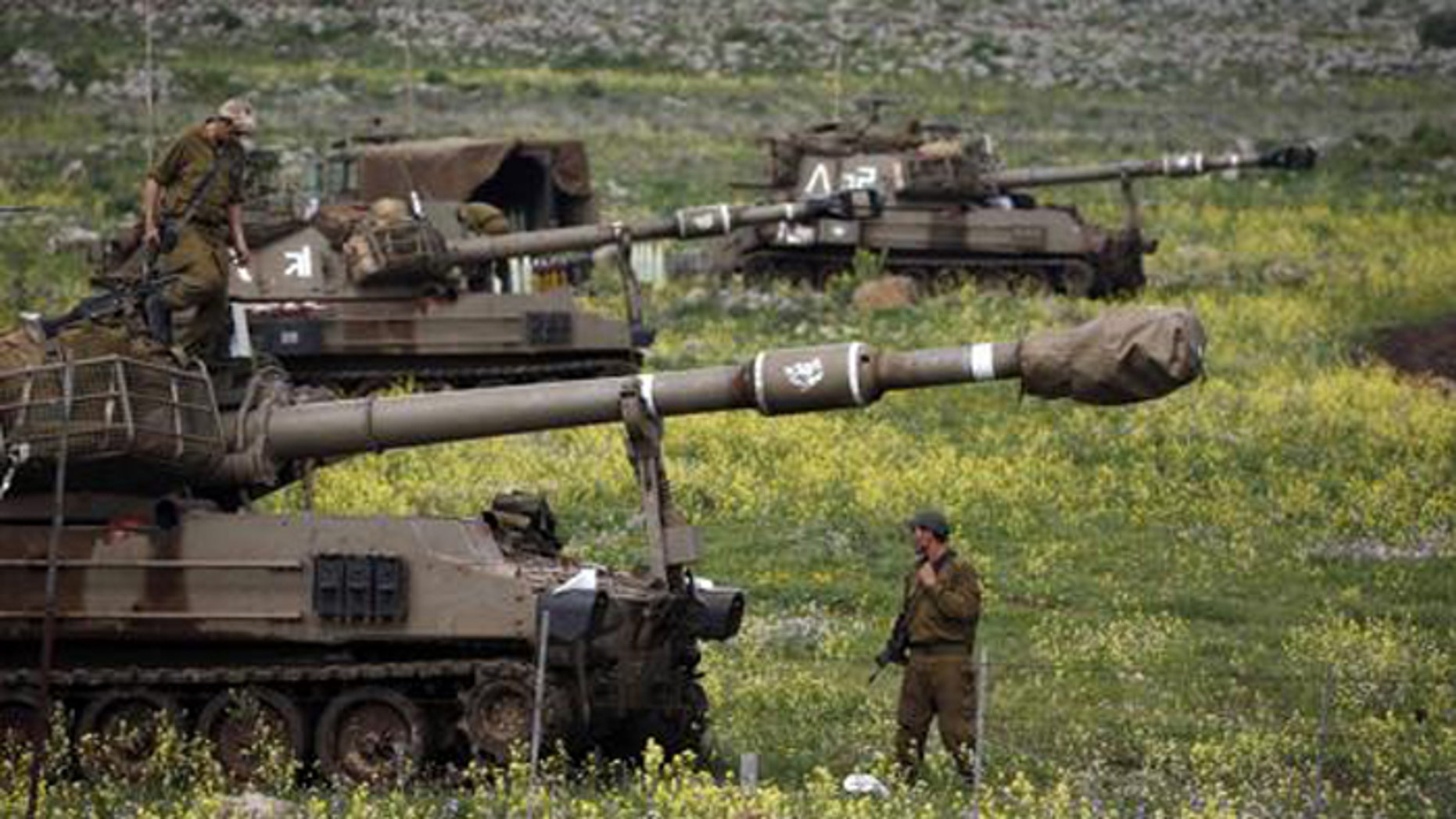 Israeli soldier stands beside a mobile artillery unit in the Golan Heights March 19, after Israel launched air strikes against Syrian military sites in response to a roadside bombing that wounded four of its soldiers. (Reuters)