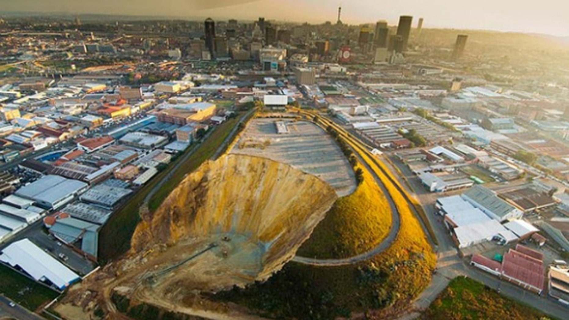 Johannesburg's landmark Top Star  mine waste dump, shown here during the early stages of removal, once hosted a drive-in movie theater. Now it is gone, and the land reclaimed. (Courtesy: DRD Gold)
