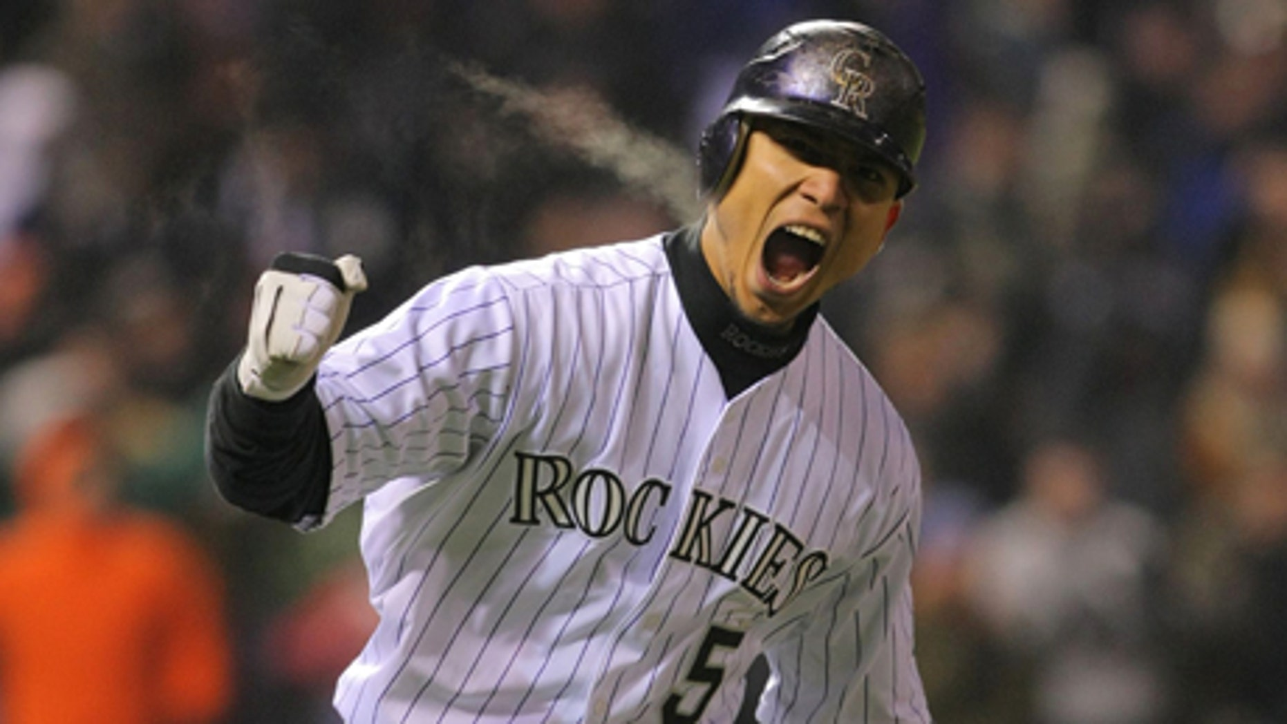 DENVER - OCTOBER 11:  Carlos Gonzalez #5 of the Colorado Rockies reacts after hitting a home run in the bottom of the fourth inning against the Philadelphia Phillies in Game Three of the NLDS during the 2009 MLB Playoffs at Coors Field on October 11, 2009 in Denver, Colorado.  (Photo by Doug Pensinger/ Getty Images)