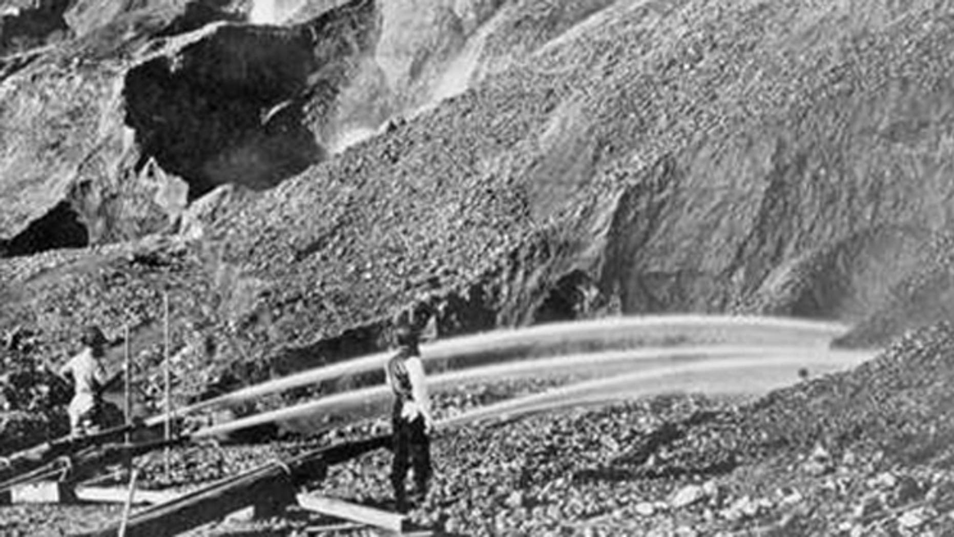 View of gold miners excavating an eroded bluff with jets of water at a placer mine in Dutch Flat, California, between 1857 and 1870.