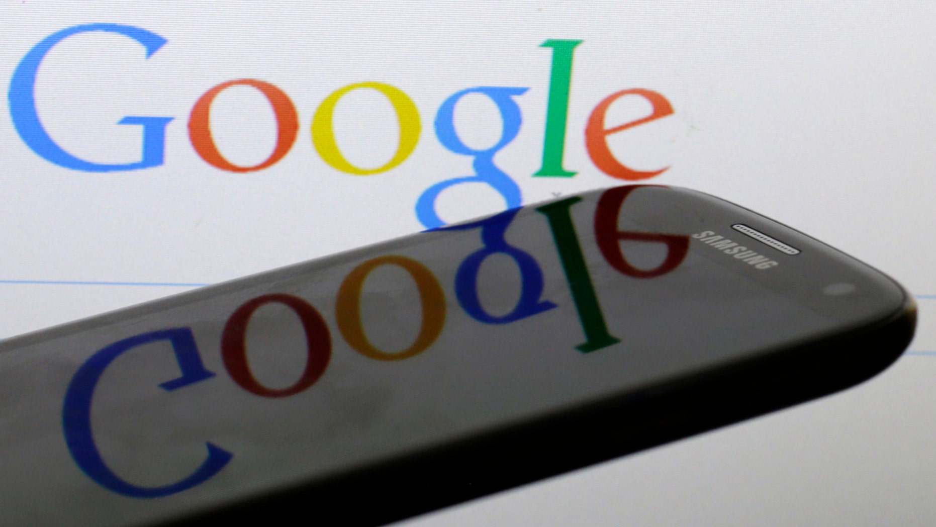 A Google logo is reflected on the screen of a Samsung Galaxy S4 smartphone in this photo illustration taken in Prague January 31, 2014. Google Inc and Samsung Electronics Co Ltd, which are frequently involved in patent infringement lawsuits but not against each other, announced on January 26, 2014 that they have reached a global patent cross-licensing agreement. Picture taken January 31.   REUTERS/David W Cerny (CZECH REPUBLIC - Tags: BUSINESS TELECOMS SCIENCE TECHNOLOGY LOGO)