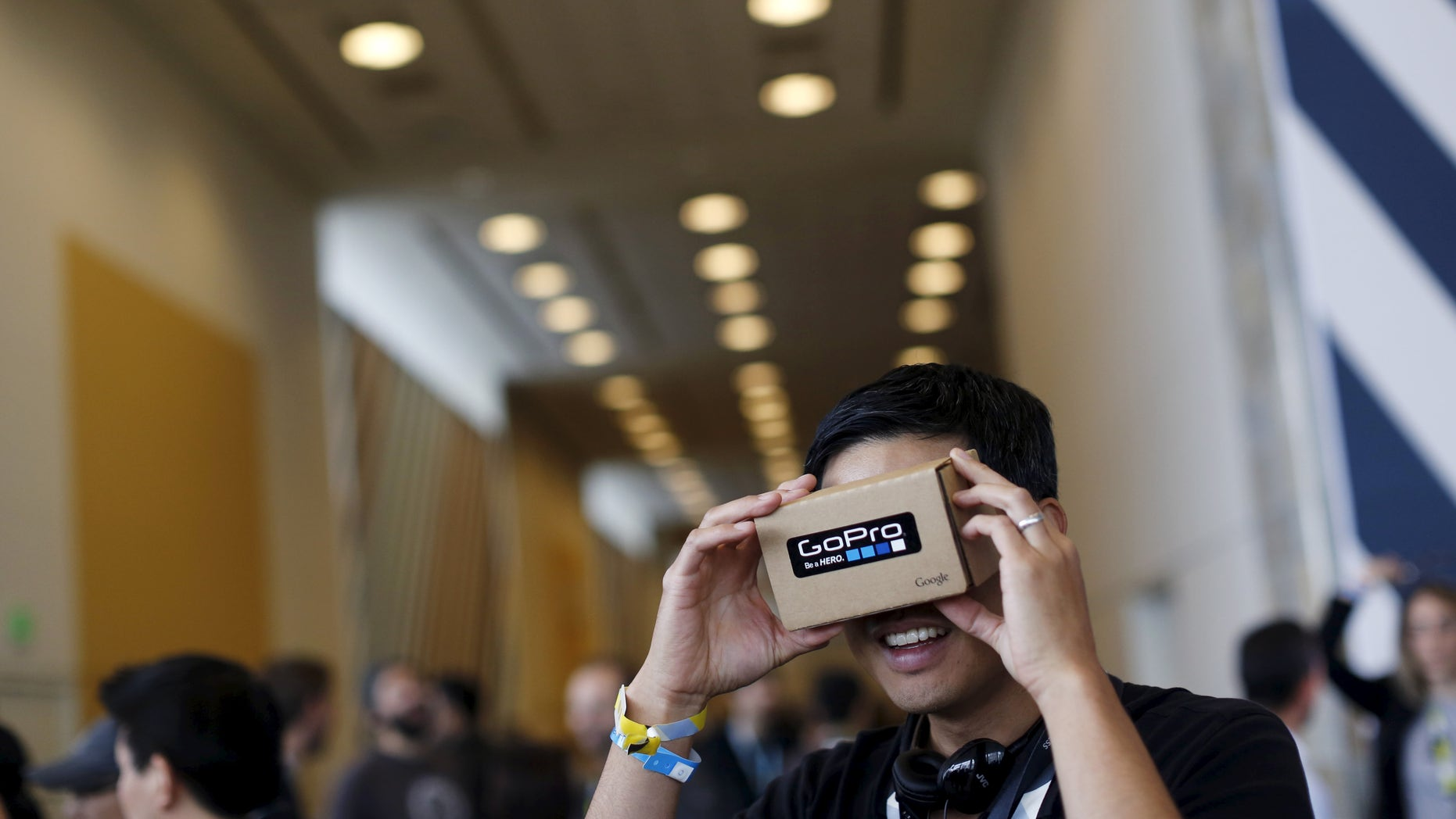 """File photo - A conference attendee looks through """"Cardboard,"""" a viewer that enables the user to view content from a smart phone in 3D, during the Google I/O developers conference in San Francisco, Calif. May 28, 2015. (REUTERS/Robert Galbraith)"""