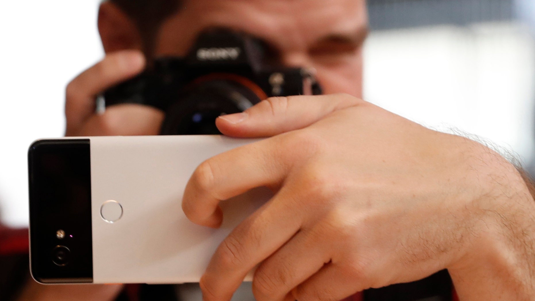 File photo: A man takes a photo of a Google Pixel 2 phone during a launch event in San Francisco, California, U.S. October 4, 2017. REUTERS/Stephen Lam