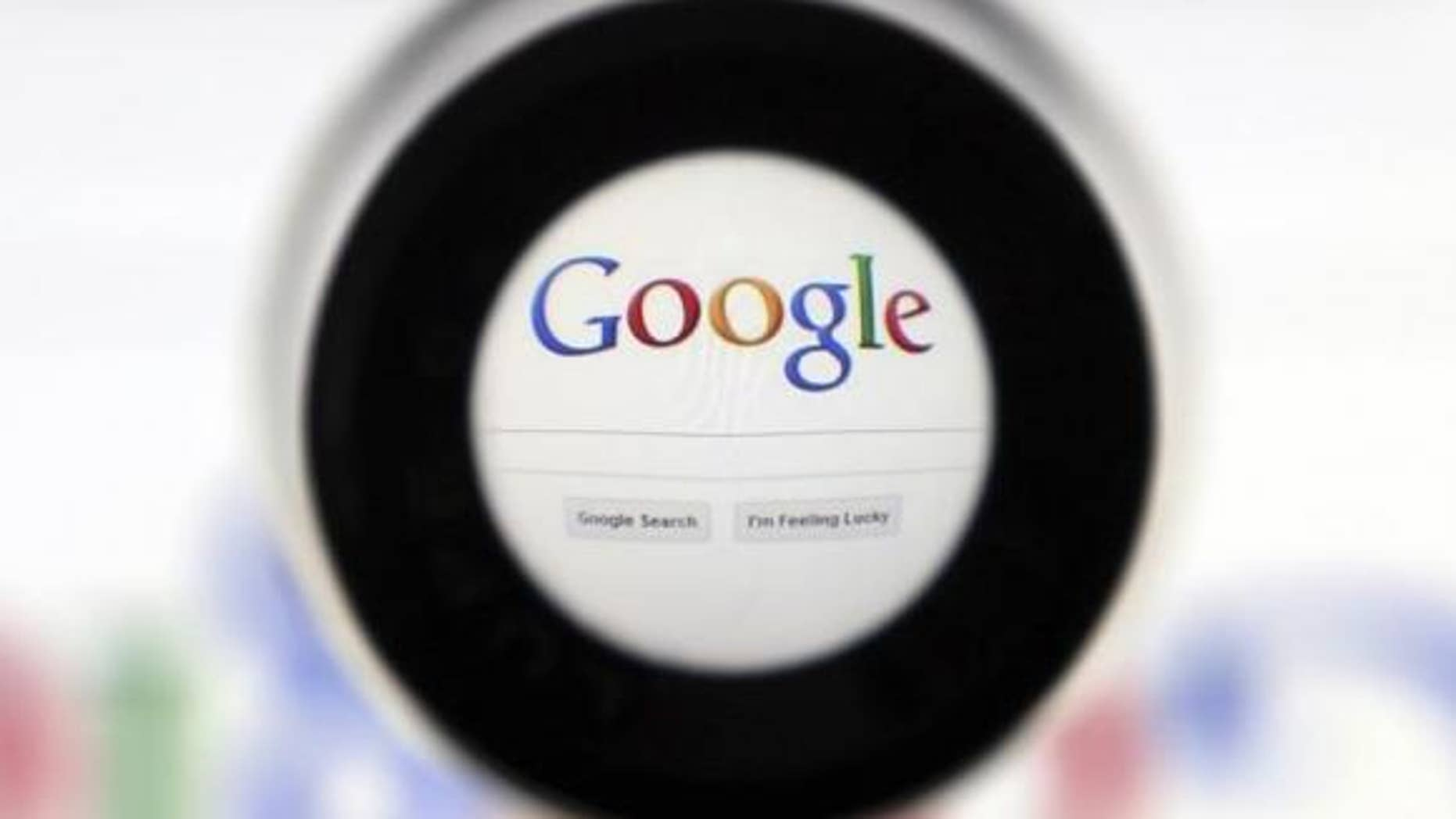 May 30, 2014: A file photo of a Google search page is seen through a magnifying glass in this photo illustration taken in Brussels.