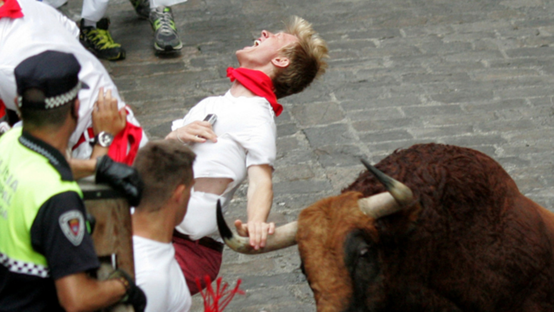 """July 12, 2013: A runner is gored by an """"El Pilar"""" fighting bull during the running of the bulls at the San Fermin festival, in Pamplona, Spain."""