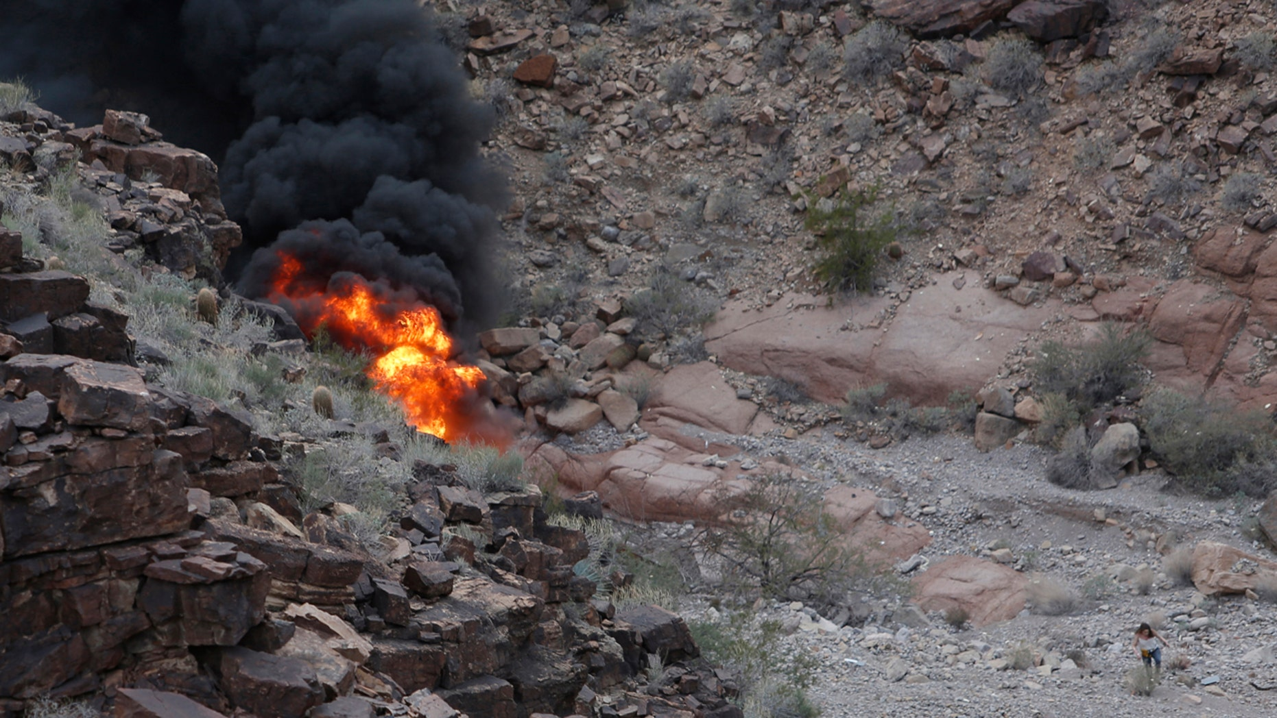 In this Saturday, Feb. 10, 2018, photo, a survivor, lower right, walks away from the scene of a deadly tour helicopter crash along the jagged rocks of the Grand Canyon, in Arizona. (Teddy Fujimoto via AP)