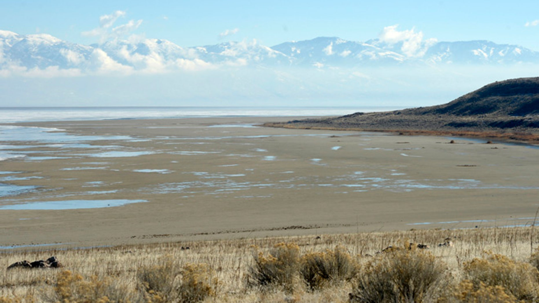 In this Wednesday Jan. 21, 2015, file photo, a view from the shore of Antelope Island looking east toward the Wasatch Mountains shows mudflats that are usually submerged by water of the Great Salt Lake in Utah.