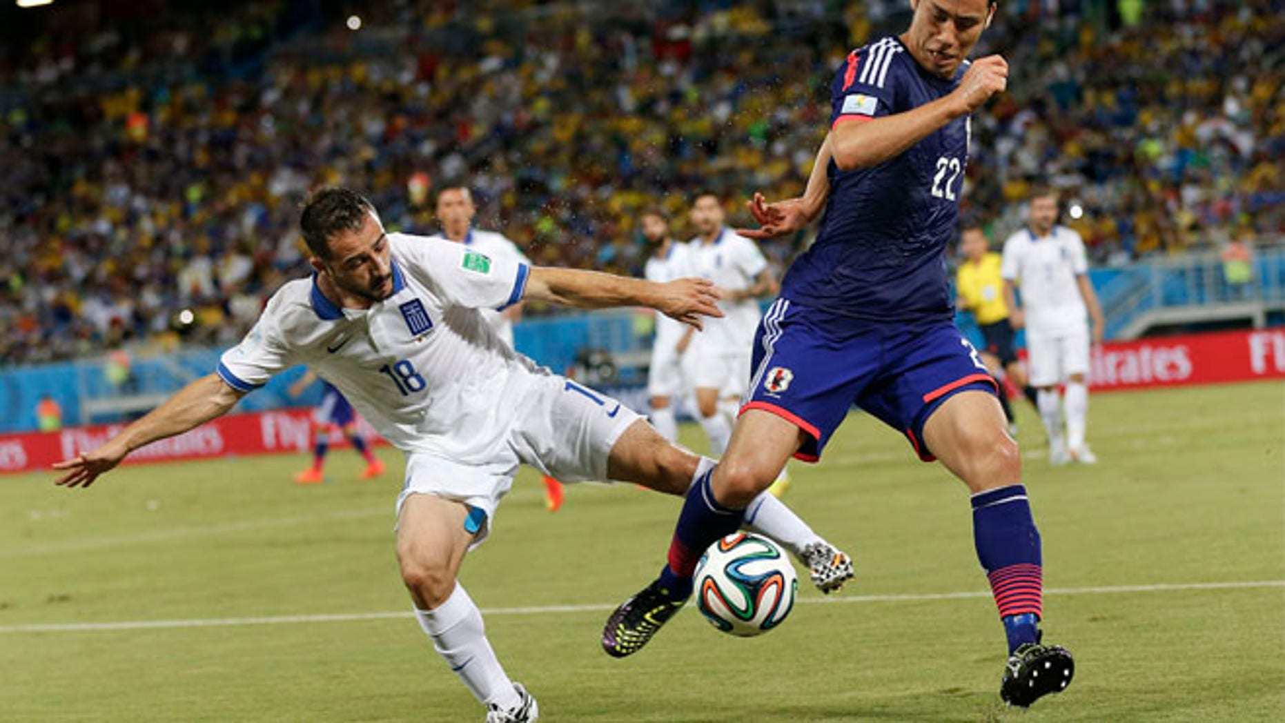June 19, 2014: Greece's Giannis Fetfatzidis, left, challenges Japan's Maya Yoshida during the group C World Cup soccer match between Japan and Greece at the Arena das Dunas in Natal, Brazil.