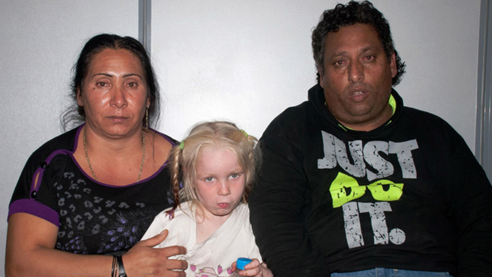 """Oct. 17, 2013: In this police handout photo Christos Salis, 39, right, and his companion Eleftheria Dimopoulou, 40, or Selini Sali as the woman has two separate sets of identity papers, pose with the little girl only known as """"Maria"""" in the Larisa regional police headquarters, Greece."""