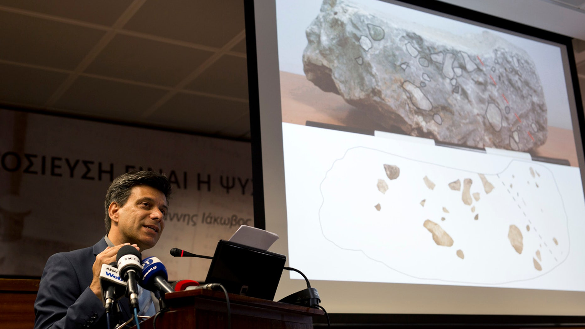 June 14, 2016: Greek archaeologist Christofilis Maggidis speaks as a photograph of a stone he believes belonged to the lost royal throne in the ancient palace of Mycenae, heart of the Mycenaean civilization, in southern Greece, during a press conference in Athens.