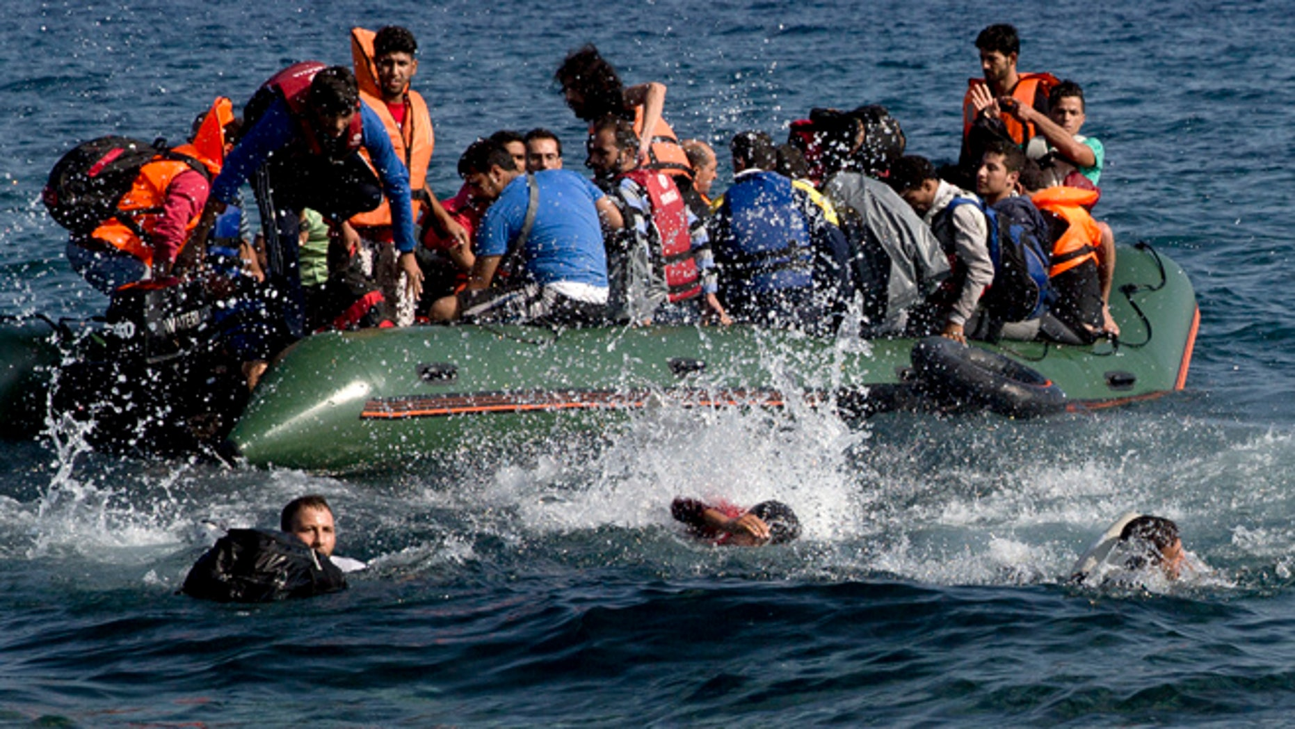 Sept. 20, 2015: Refugees whose boat stalled at sea while crossing from Turkey to Greece swim to approach the shore of the island of Lesbos, Greece.