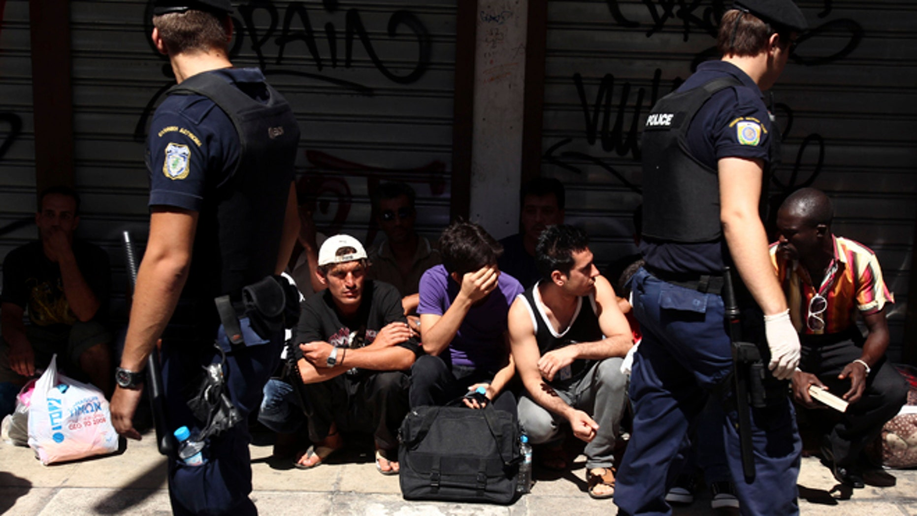 August 5, 2012: Police detain a group of migrants in central Athens.