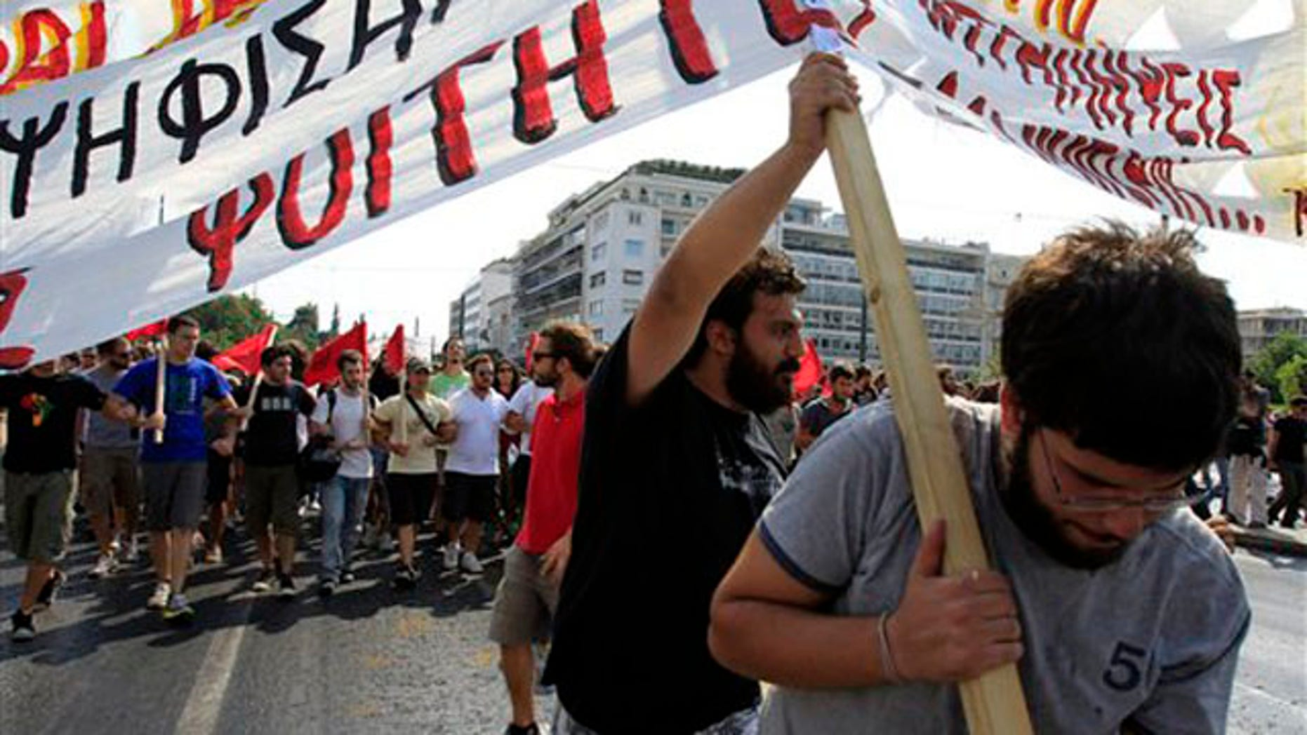 University students try to hold a banner during a protest in Athens, Thursday, Sept. 8, 2011.