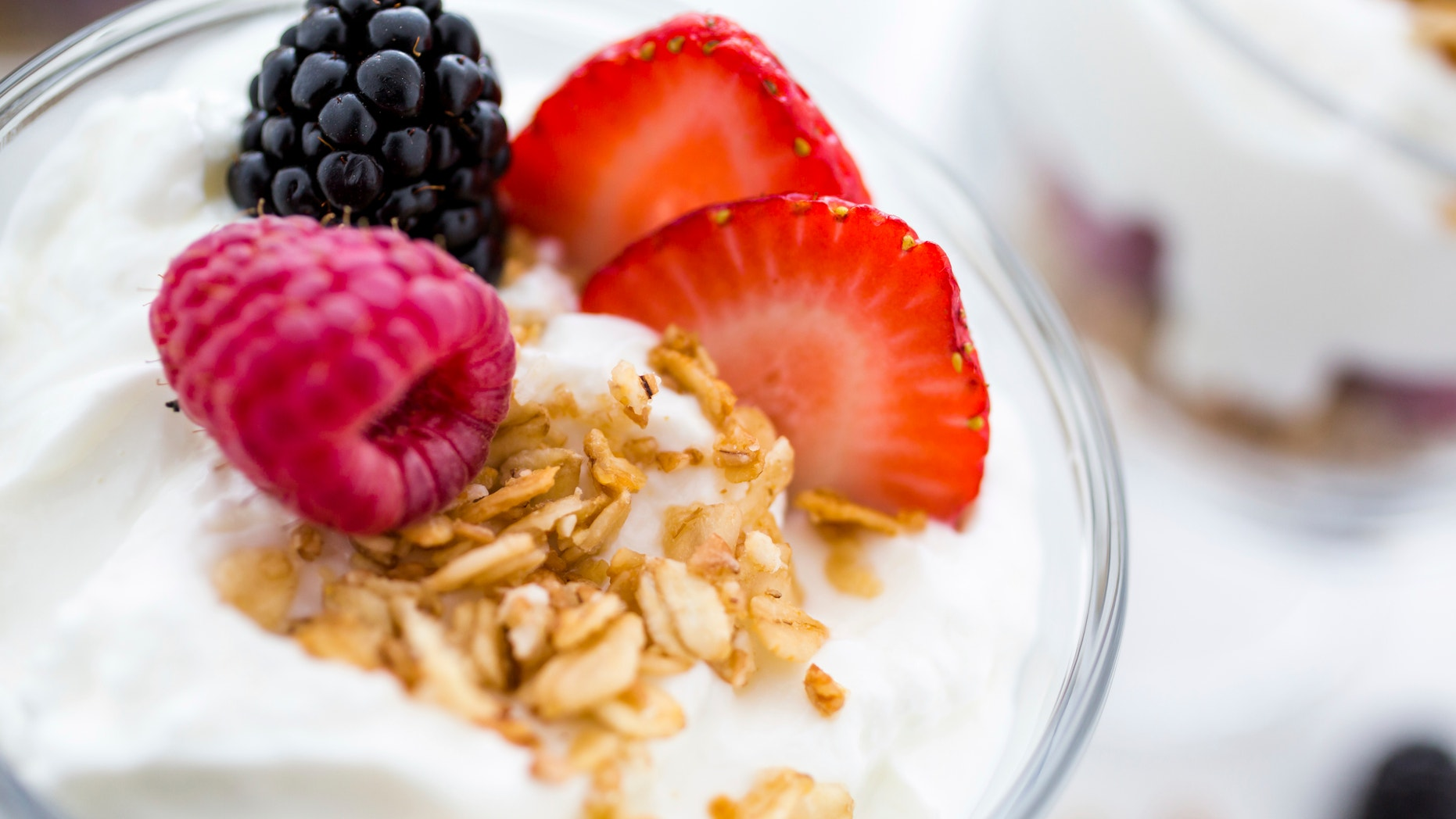 Breakfast parfait made from Greek yogurt and granola topped with fresh berries.