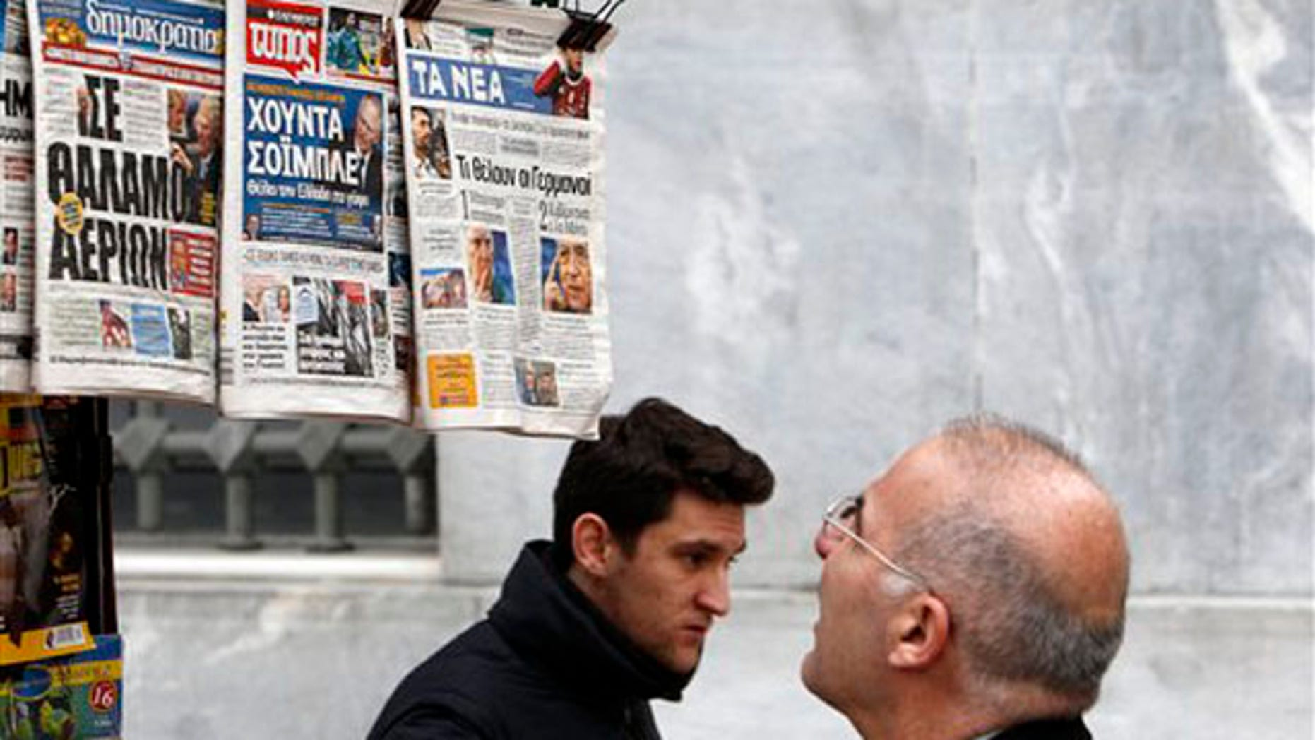 Feb. 16, 2012: A man reads the front pages of three Greek newspapers in Athens. Mounting confusion over whether Greece will get vital bailout cash to avoid defaulting next month is rekindling fears that Europe's debt crisis will spread to bigger countries like Italy.