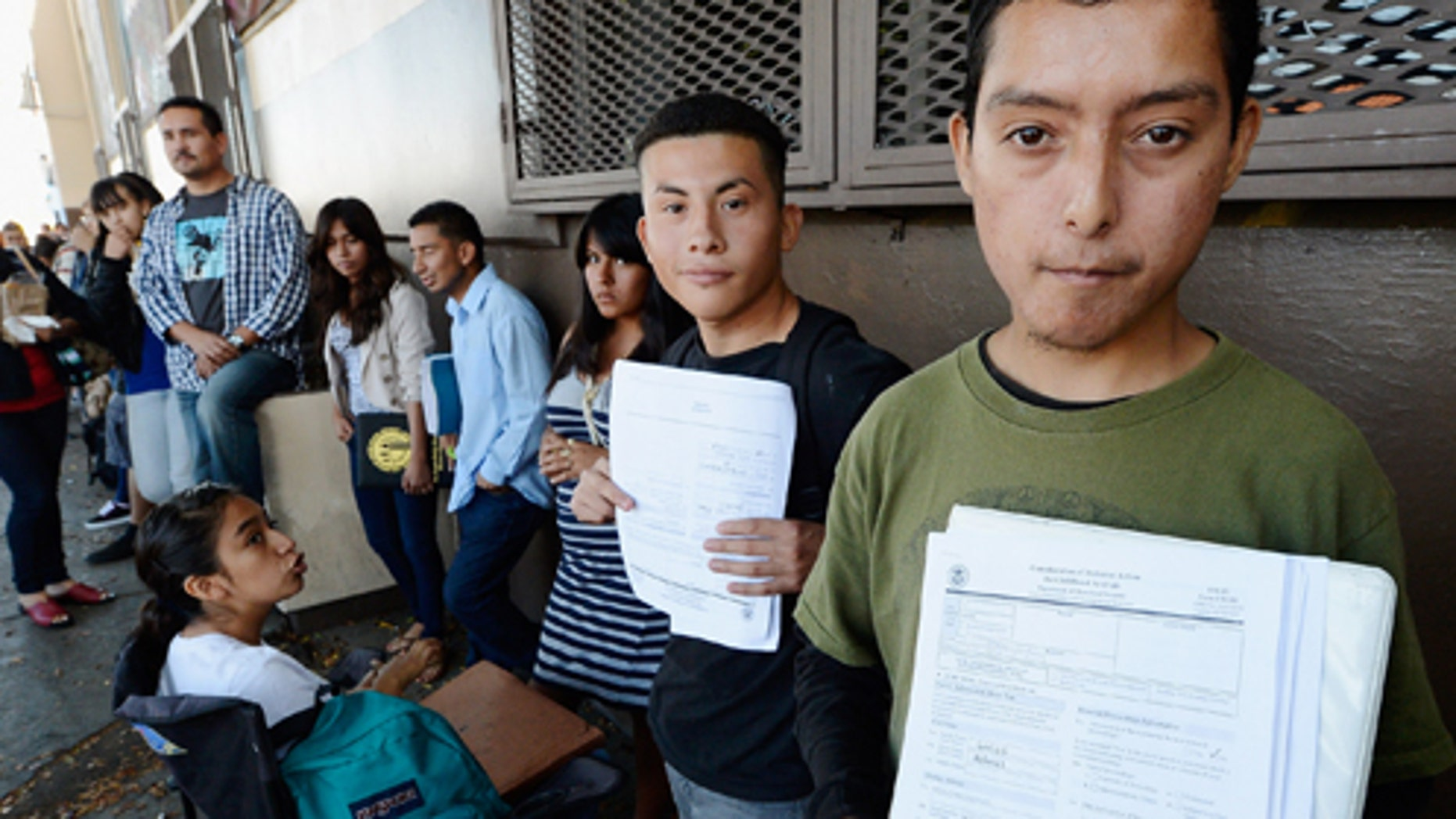 LOS ANGELES, CA - AUGUST 15: Roberto Larios, 21, (R) holds Deferred Action for Childhood Arrival application as he waits in line with hundreds of fellow undocumanted immigrants at the Coalition for Humane Immigrant Rights of Los Angeles offices to apply for deportation reprieve on August 15, 2012 in Los Angeles, California. Under a new program established by the Obama administration undocumented youth who qualify for the program, called Deferred Action for Childhood Arrivals, can file applications from the U.S. Citizenship and Immigration Services website to avoid deportation and obtain the right to work  (Photo by Kevork Djansezian/Getty Images)