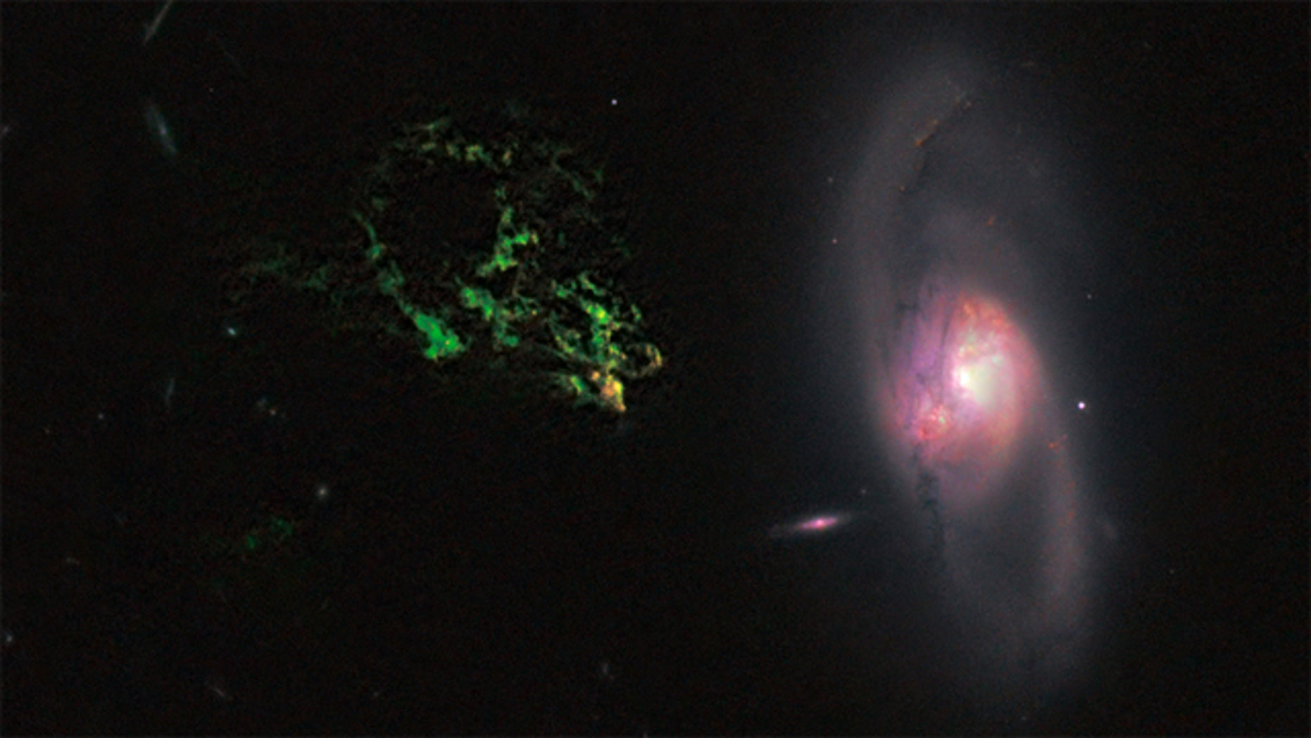 In this image by NASA's Hubble Space Telescope, an unusual, ghostly green blob of gas appears to float near a normal-looking spiral galaxy. The bizarre object, dubbed Hanny's Voorwerp (Hanny's Object in Dutch), is the only visible part of a 300,000-light-year-long streamer of gas stretching around the galaxy, called IC 2497.