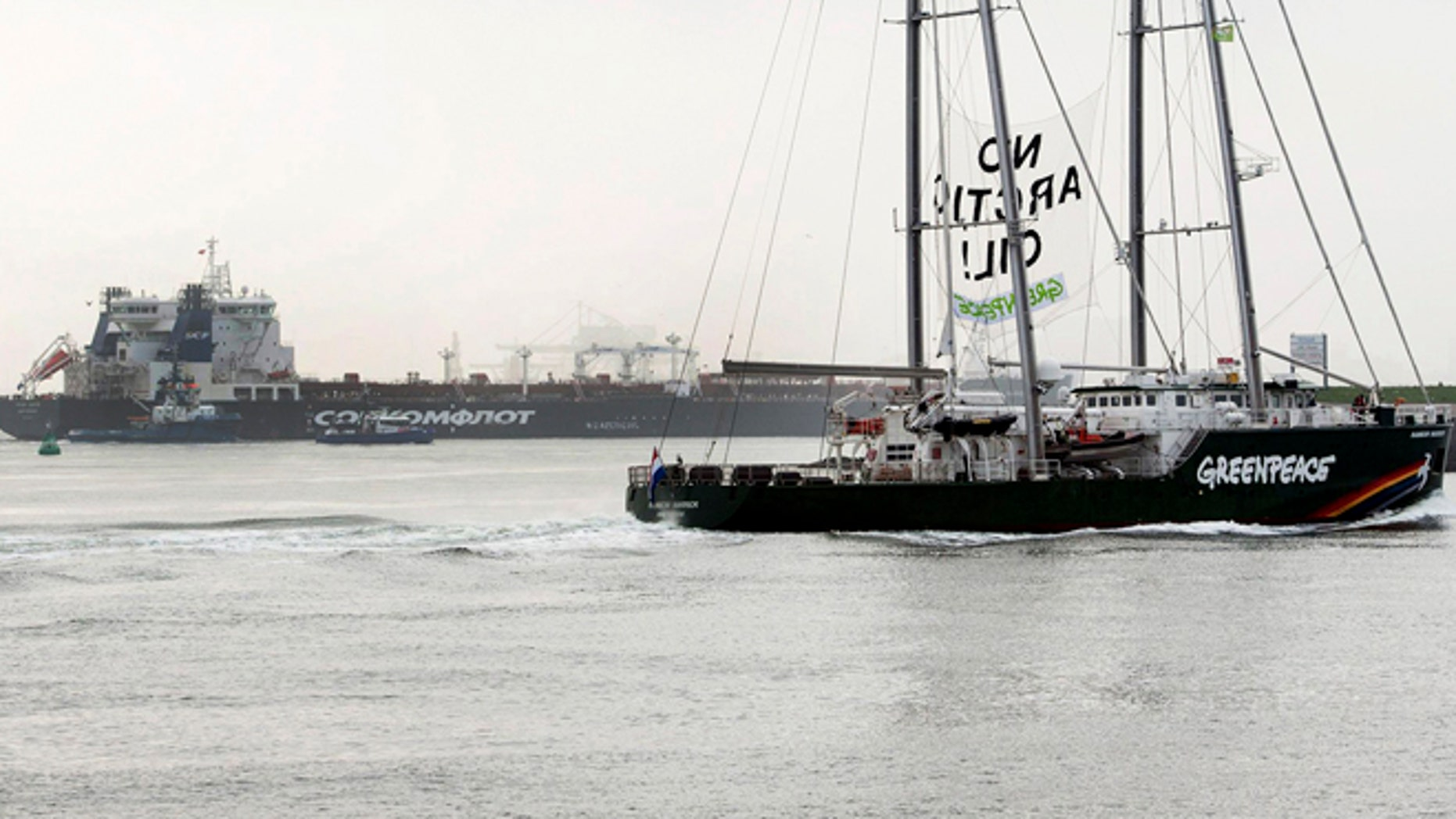 """May 1, 2014: This image made available by environmental organization Greenpeace shows the Greenpeace ship Rainbow Warrior showing a banner reading: """"No Arctic Oil"""" as Greenpeace activists aboard inflatable boats paint """"No Arctic Oil"""" on the side of the Mikhail Ulyanov oil tanker, seen in the background, in Rotterdam, Netherlands."""