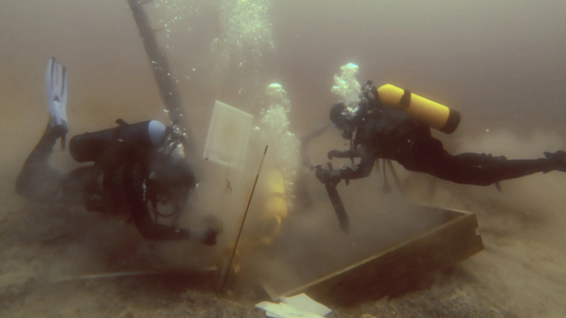 June 16, 2013: Divers inspect a hole being dug beside a wooden beam jutting from the floor of Lake Michigan during exploration for the 17th century ship the Griffin.