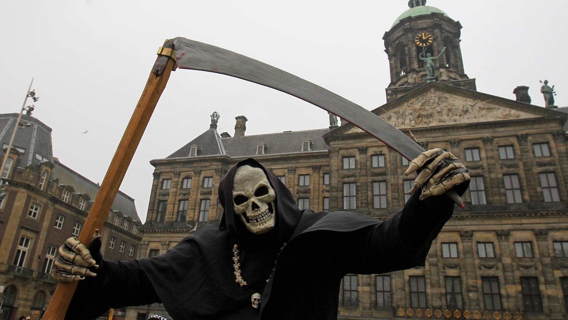 File photo - A street artist dressed as the grim reaper performs in front of the Dutch Royal Palace on Dam Square in Amsterdam March 19, 2013. (REUTERS/Yves Herman)