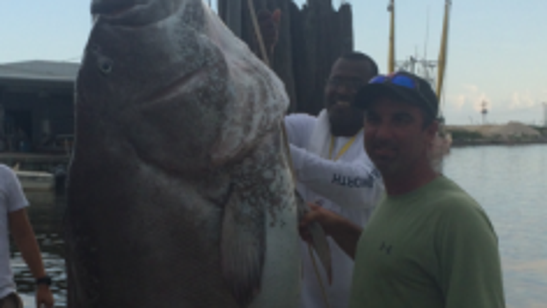 Simon Guidry poses with the 6-foot, 10-inch 305-pound Warsaw grouper