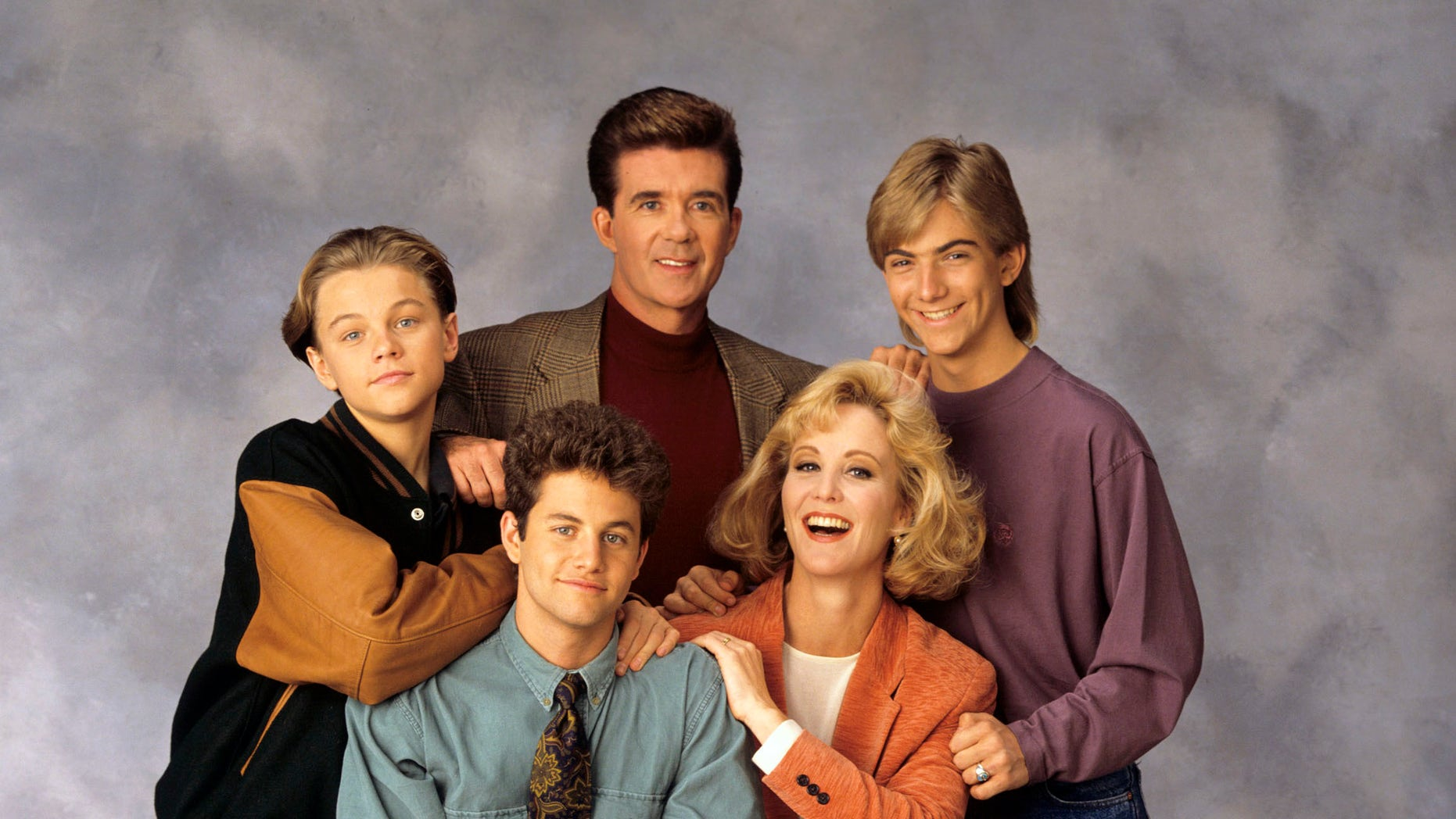 "This 1991 image released by ABC shows the cast of ""Growing Pains,"" standing from left, Leonardo DiCaprio, Alan Thicke and Jeremy Miller, with Kirk Cameron, seated center left, and Joanna Kerns, seated center right, and Tracey Gold, seated left on floor and Ashley Johnson. Thicke, who played Dr. Jason Seaver, a psychiatrist and ideal TV dad, died on Tuesday, Dec. 13, 2016."
