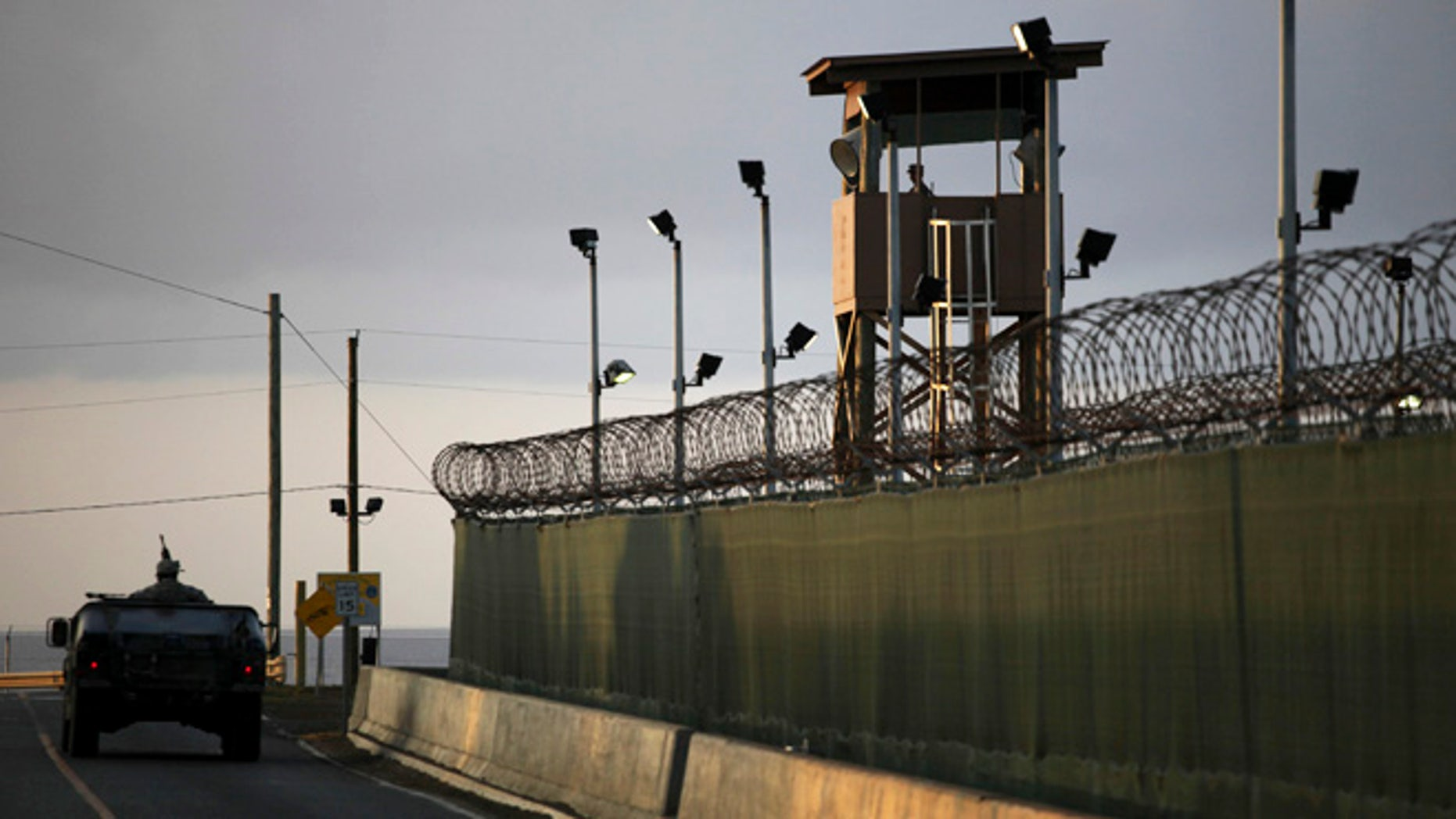 In this March 30, 2010 file photo, reviewed by the U.S. military, a U.S. trooper stands in the turret of a vehicle with a machine gun, left, as a guard looks out from a tower at the detention facility of Guantanamo Bay U.S. Naval Base in Cuba. The U.S. government has dropped its opposition to the release of a Guantanamo Bay prisoner, Ibrahim Idris, who suffers from severe psychological and physical illnesses. He will likely go back to his native Sudan.