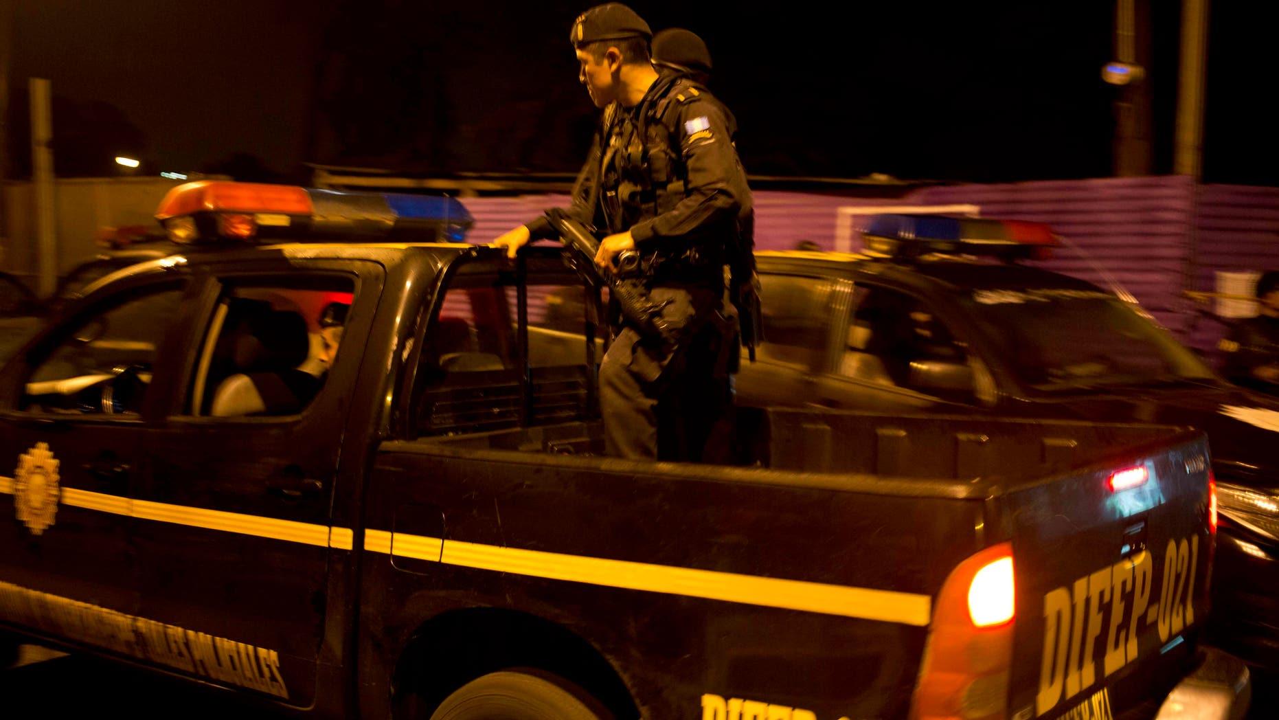 Agentes policiales patrullan cerca de la escena de un crimen en el barrio Guajitos, en las afueras de la ciudad de Guatemala, la madrugada del jueves 1 de octubre de 2015. Tres pandilleros murieron y al menos seis fueron detenidos durante un ataque simultáneo contra una estación policial y policías que realizaban patrullajes, de acuerdo con Elmer Sosa, viceministro de gobernación. (AP Foto/Moises Castillo)