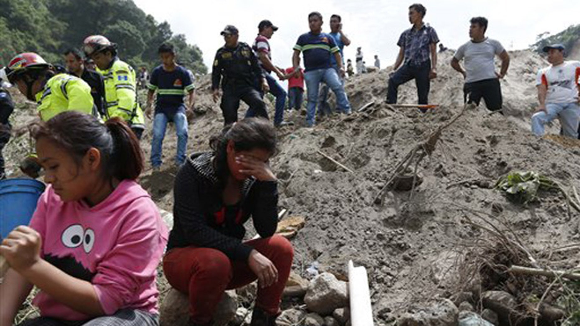 Oct. 2, 2015: Residents watch rescue efforts after a mudslide hit Santa Catarina Pinula, on the outskirts of Guatemala City. Heavy rain provoked a hillside to collapse on dozens of homes.
