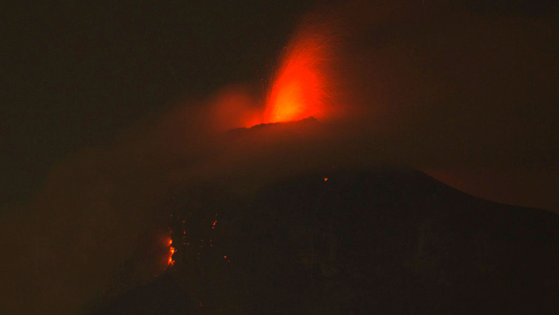 In this image taken with a long exposure, the Volcan de Fuego, or Volcano of Fire, spews molten rock from its crater in Alotenango, Guatemala, Sunday, June 3, 2018. Rescuers struggled to reach rural residents cut off by the deadly volcanic eruption Sunday. (AP Photo/Luis Soto)