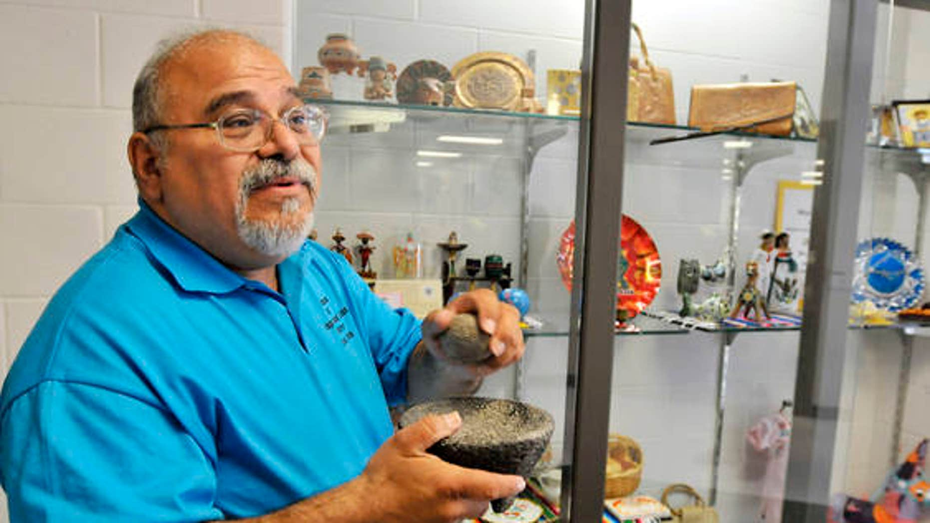 Curator Guillermo Arriaga holds a molcajete, a traditional Mexican version of mortar and pestle carved out of volcanic rock, one of the artifacts on display by the Museum of Hispanic and Latino Cultures at Southview Middle School in Lorain, Ohio.