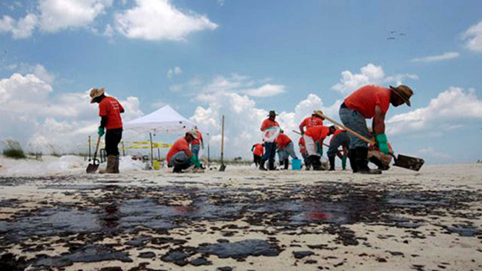 Oil cleanup workers hired by BP pick up oil on the beach in Gulf Shores, Ala., July 2. (AP Photo)