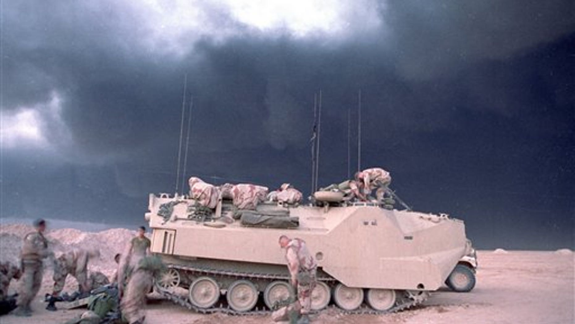 File photo from 1991 shows smoke from a burning oil well in Kuwait billowing upbehind a U.S. Marines armored vehicle.