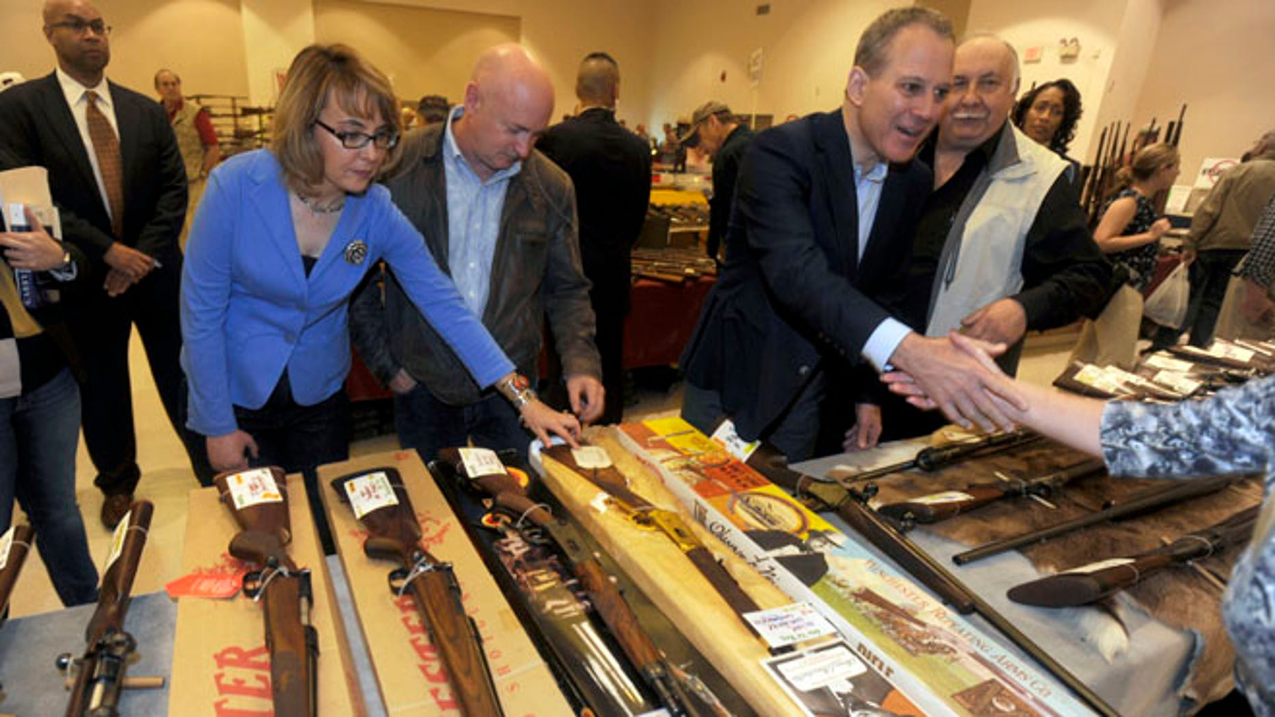 FILE: Oct. 13, 2013:  former Arizona Rep. Gabby Giffords and husband Mark Kelly, center, and New York Attorney General Eric Schneiderman, at the New EastCoast Arms Collectors Associates arms fair in Saratoga Springs, N.Y.