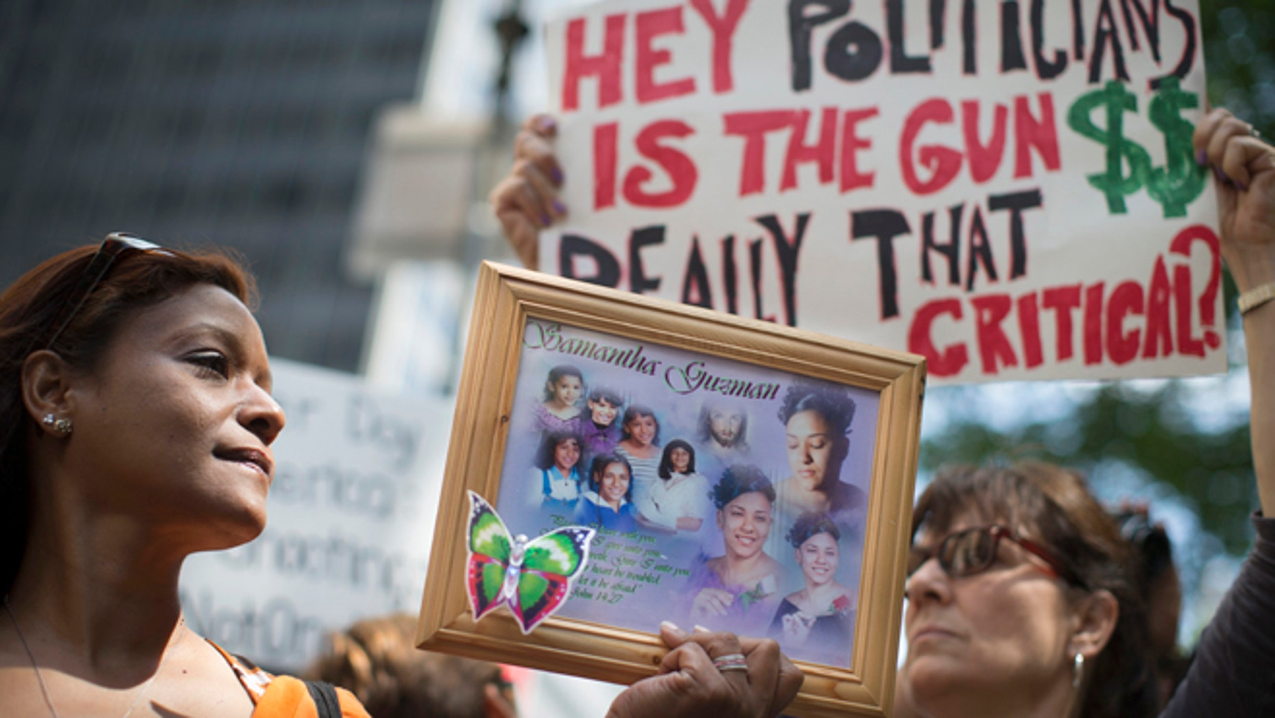 FILE: June 14, 2014: Diana Rodriguez with a picture of her daughter, a victim of gun violence, at a rally outside city hall in New York City.