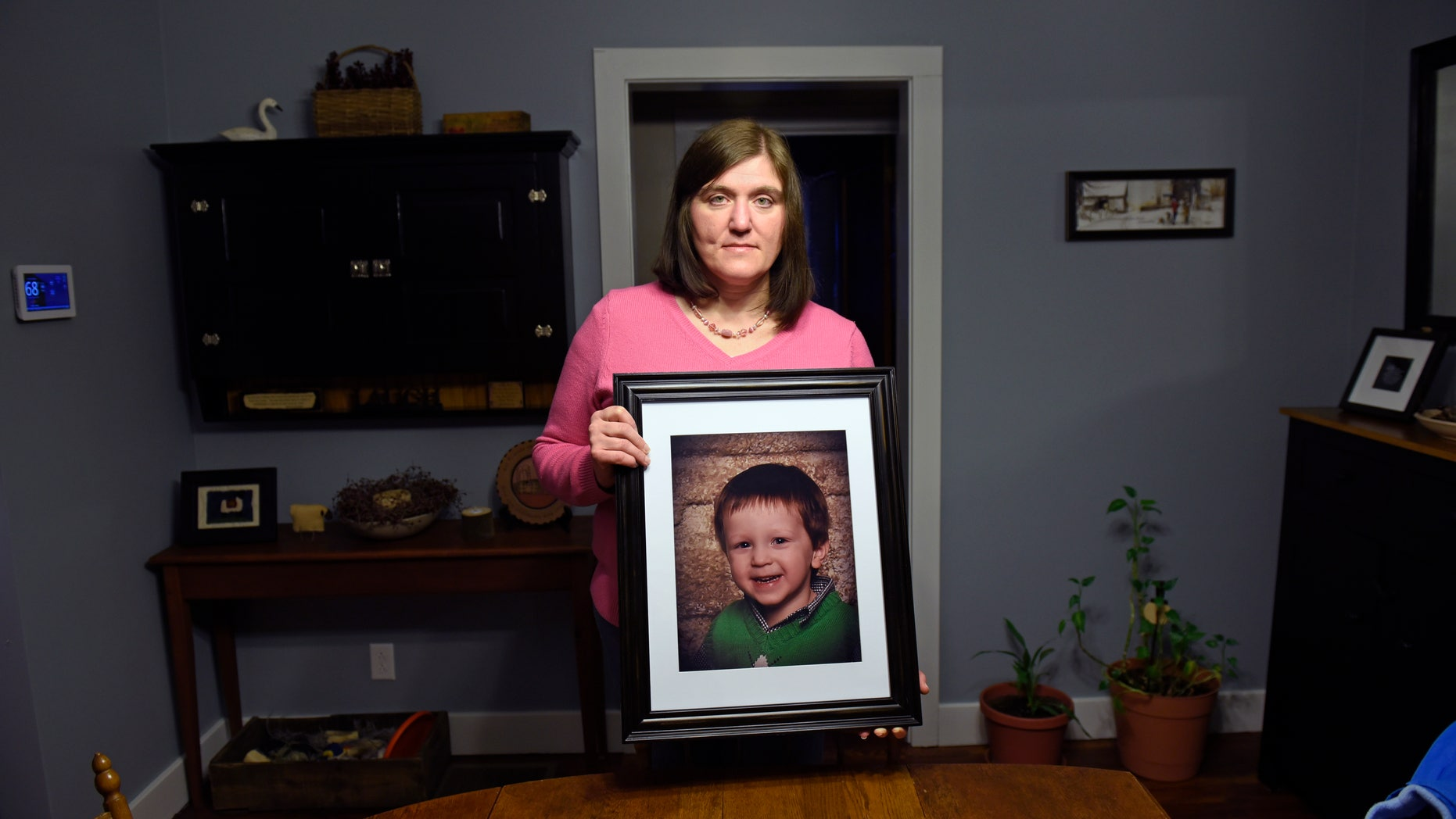 Hollie Ayers poses with a photograph of her late son, Michael, at her home in Bedford, Pa.